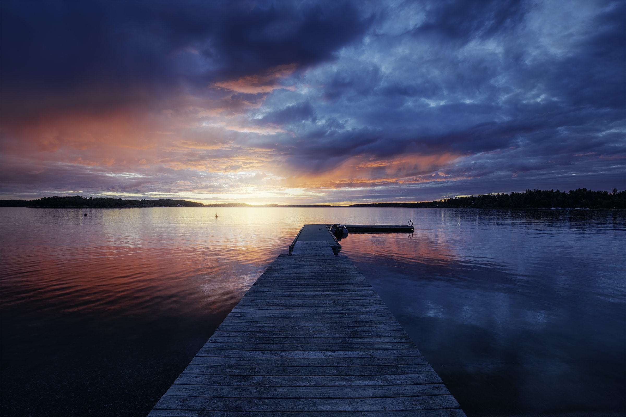 Red and blue sky over a long wooden pier on a lake during sunset
