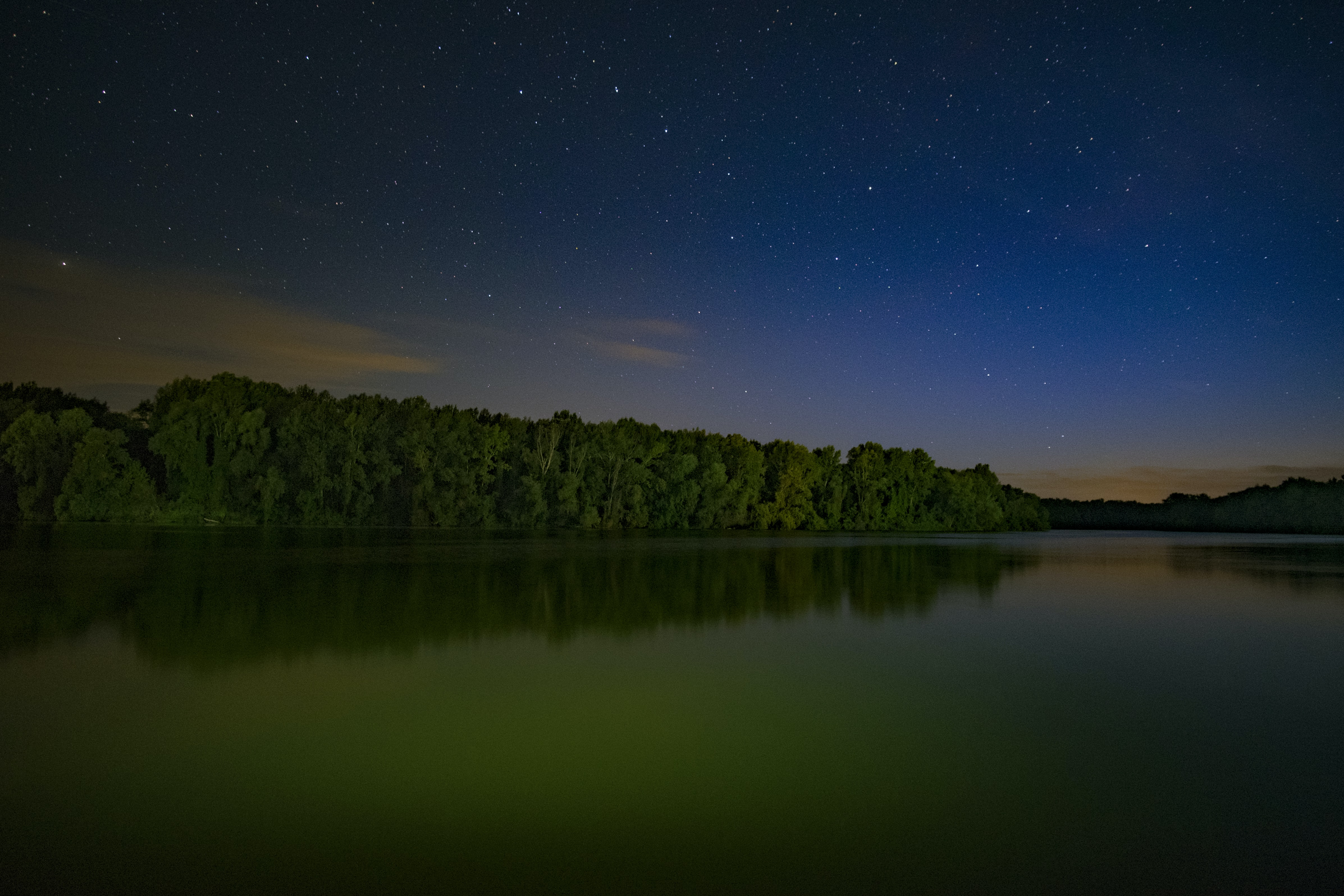 Starry sky over a lake surrounded with green forests