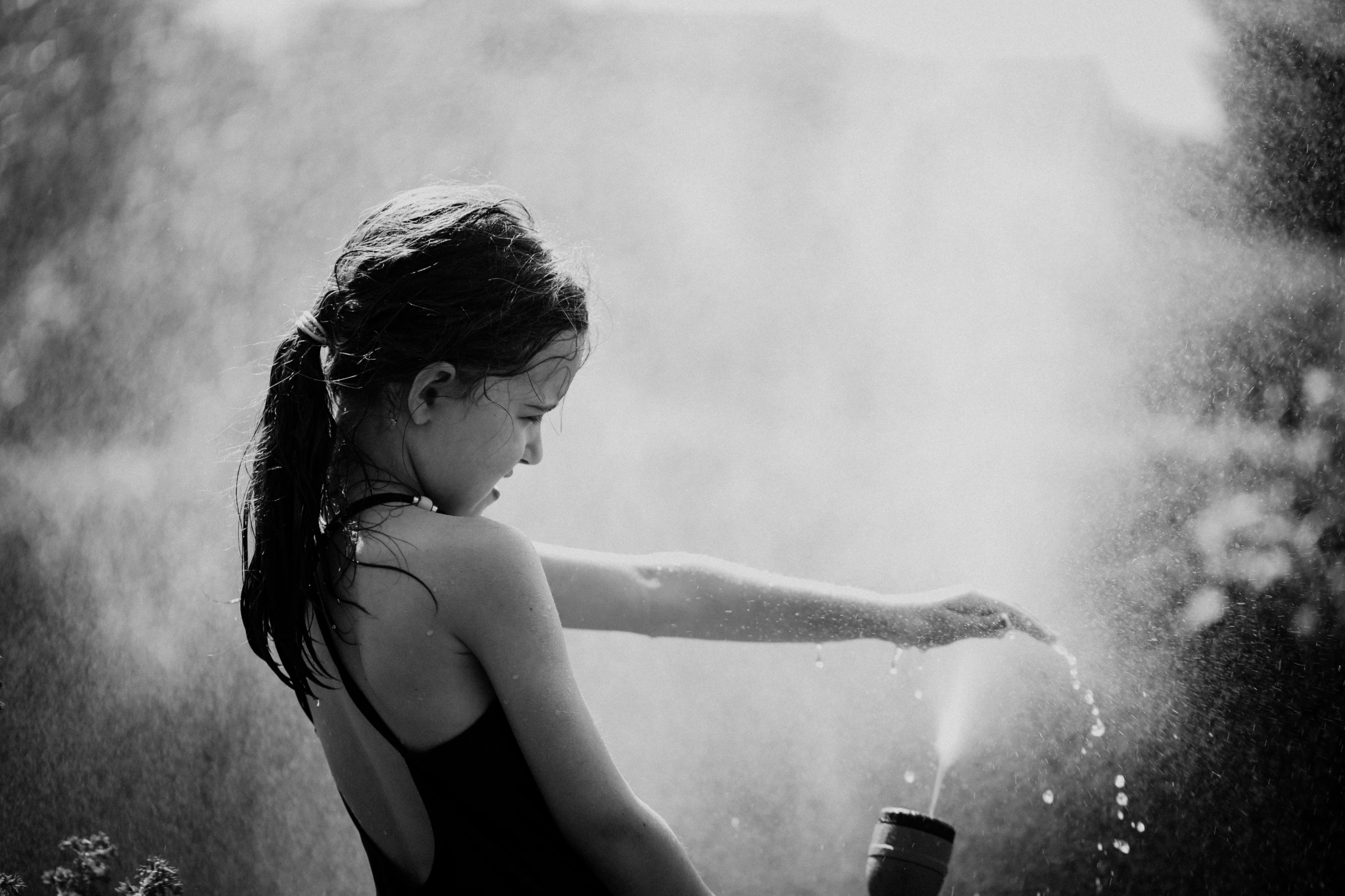grayscale photography of girl playing water