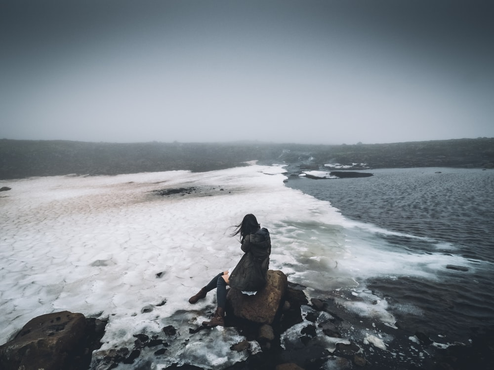 woman sitting on rock near seashore