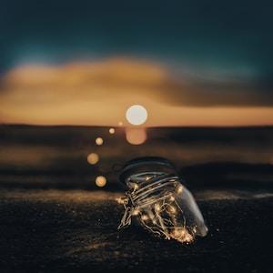 clear glass jar on sand