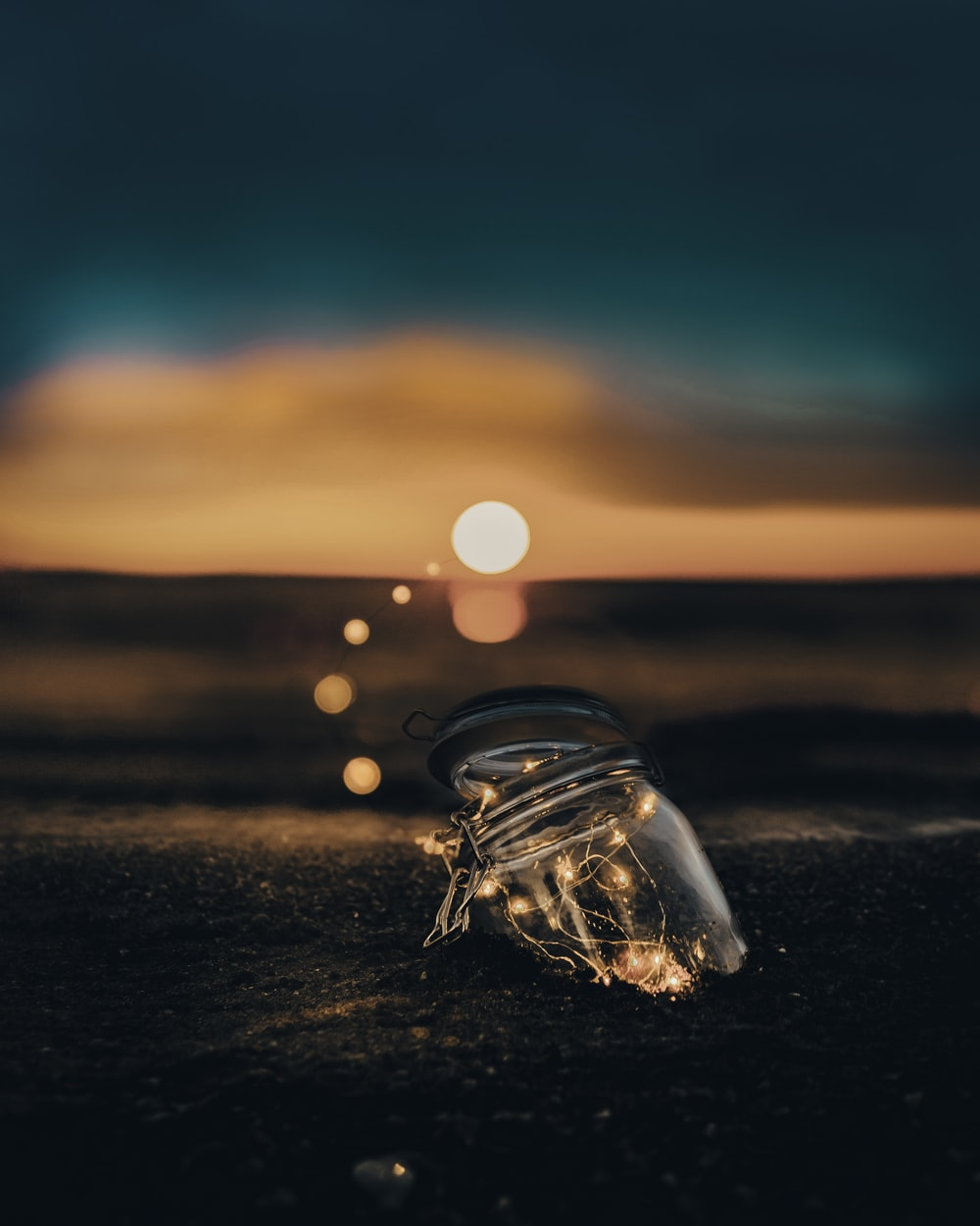 clear glass jar on sand