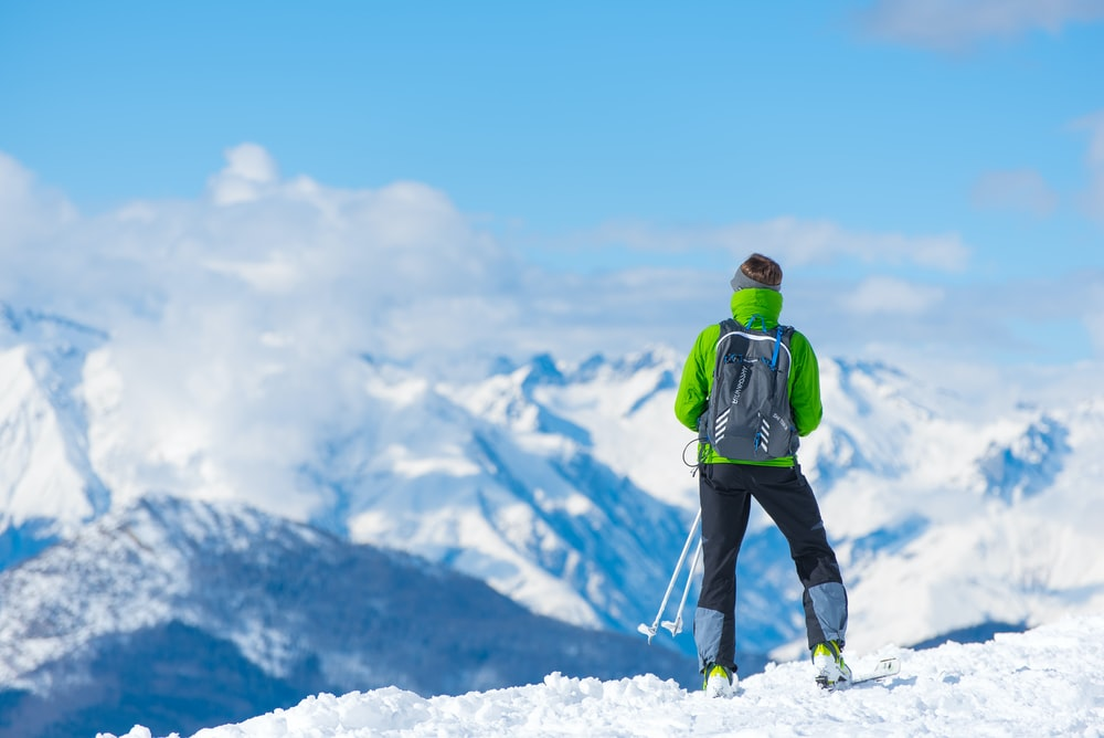 man standing on top of snow mountain