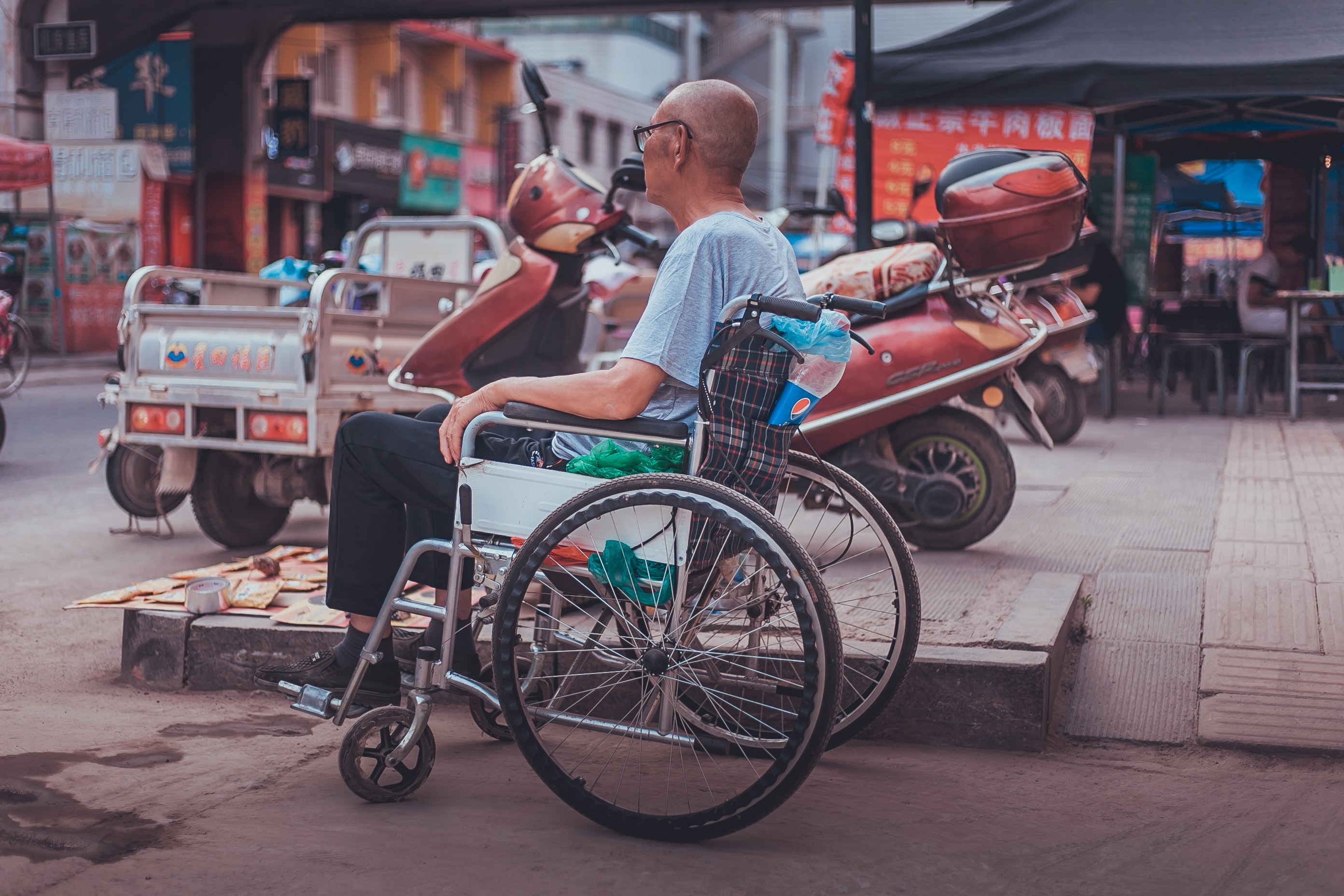 A bald man in a wheelchair at the market on a warm afternoon
