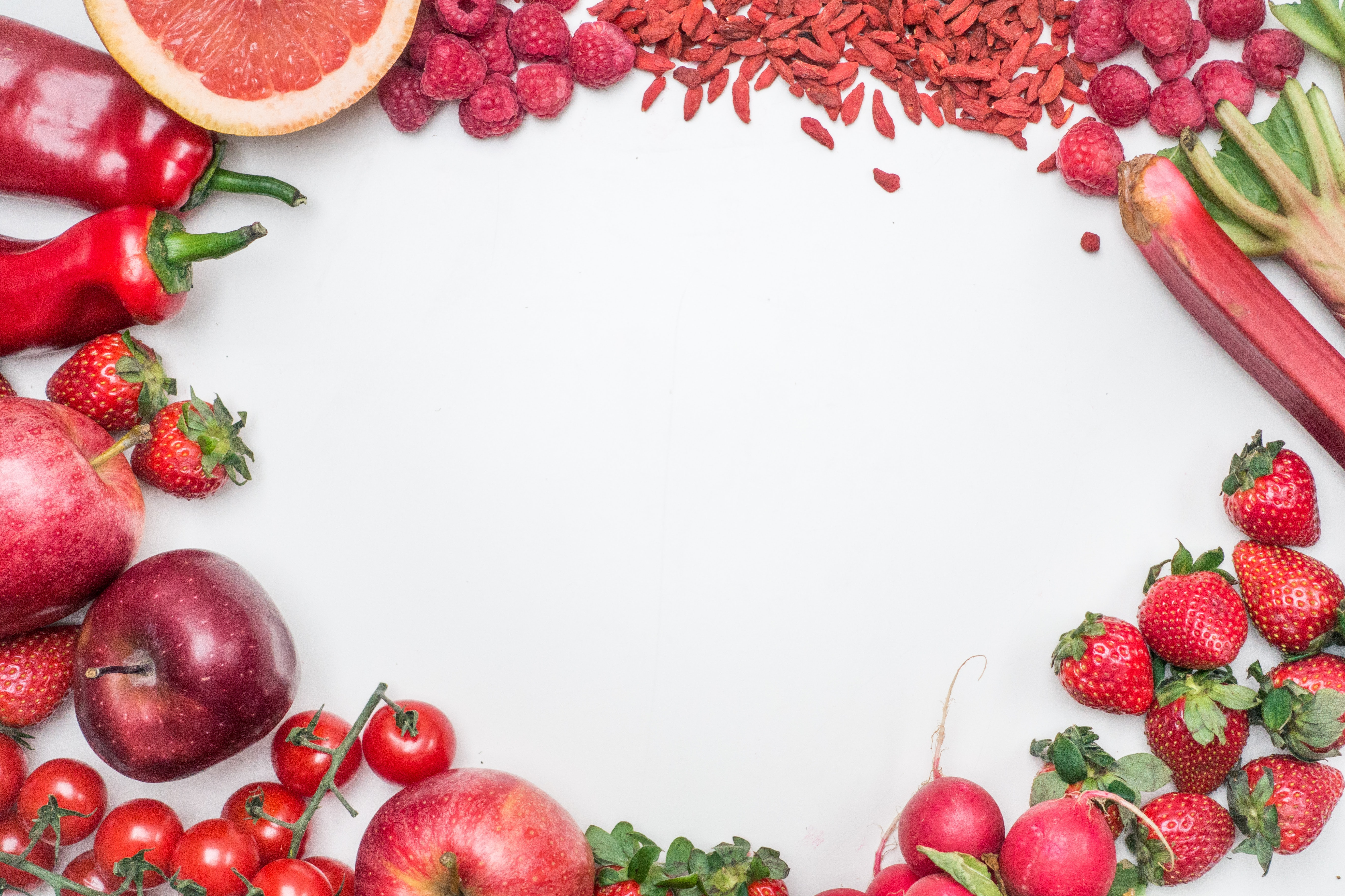 Red fruit and vegetable border with berries, chilis, and seeds on a white table
