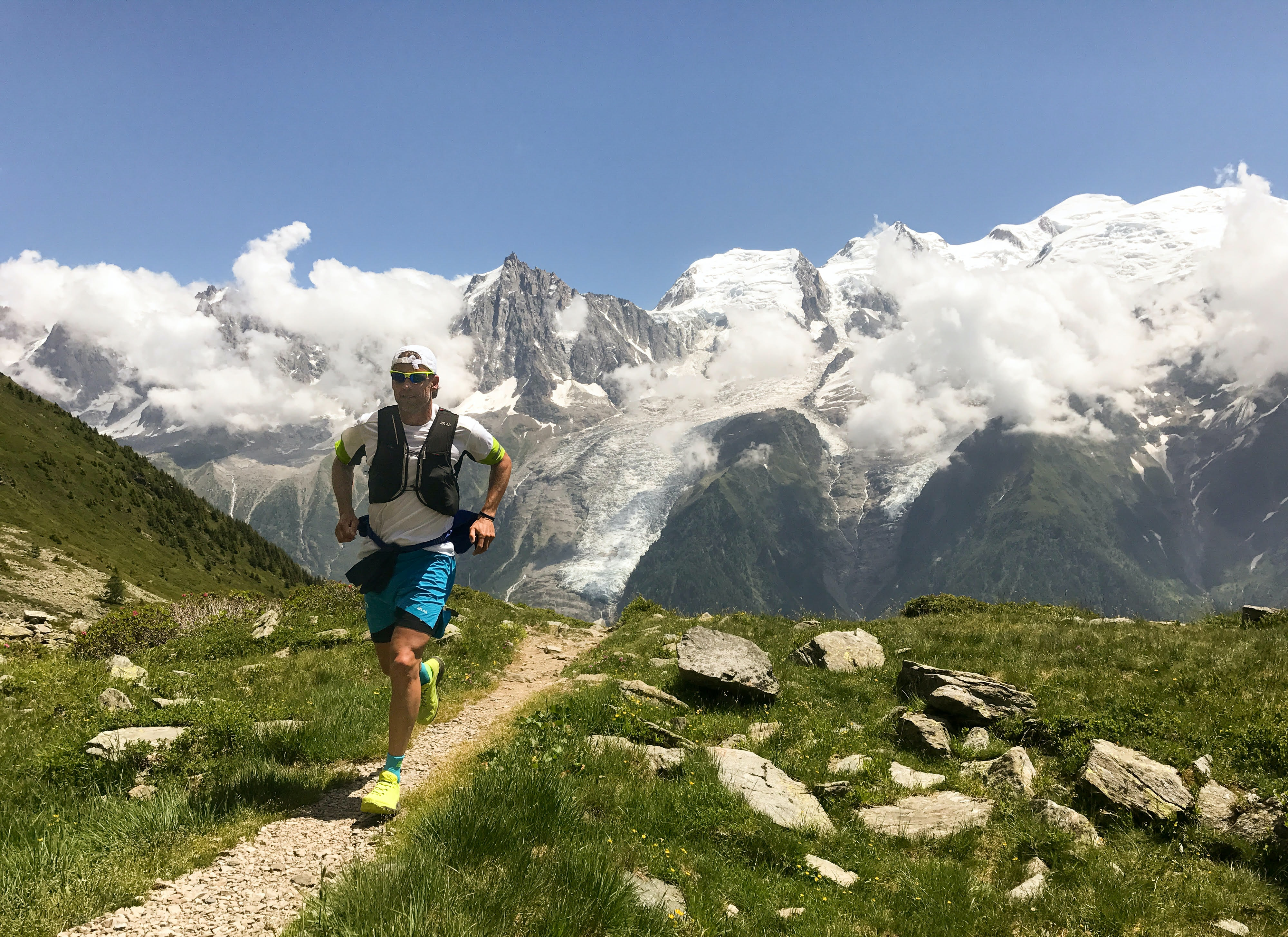A man jogging on a narrow footpath in high mountains