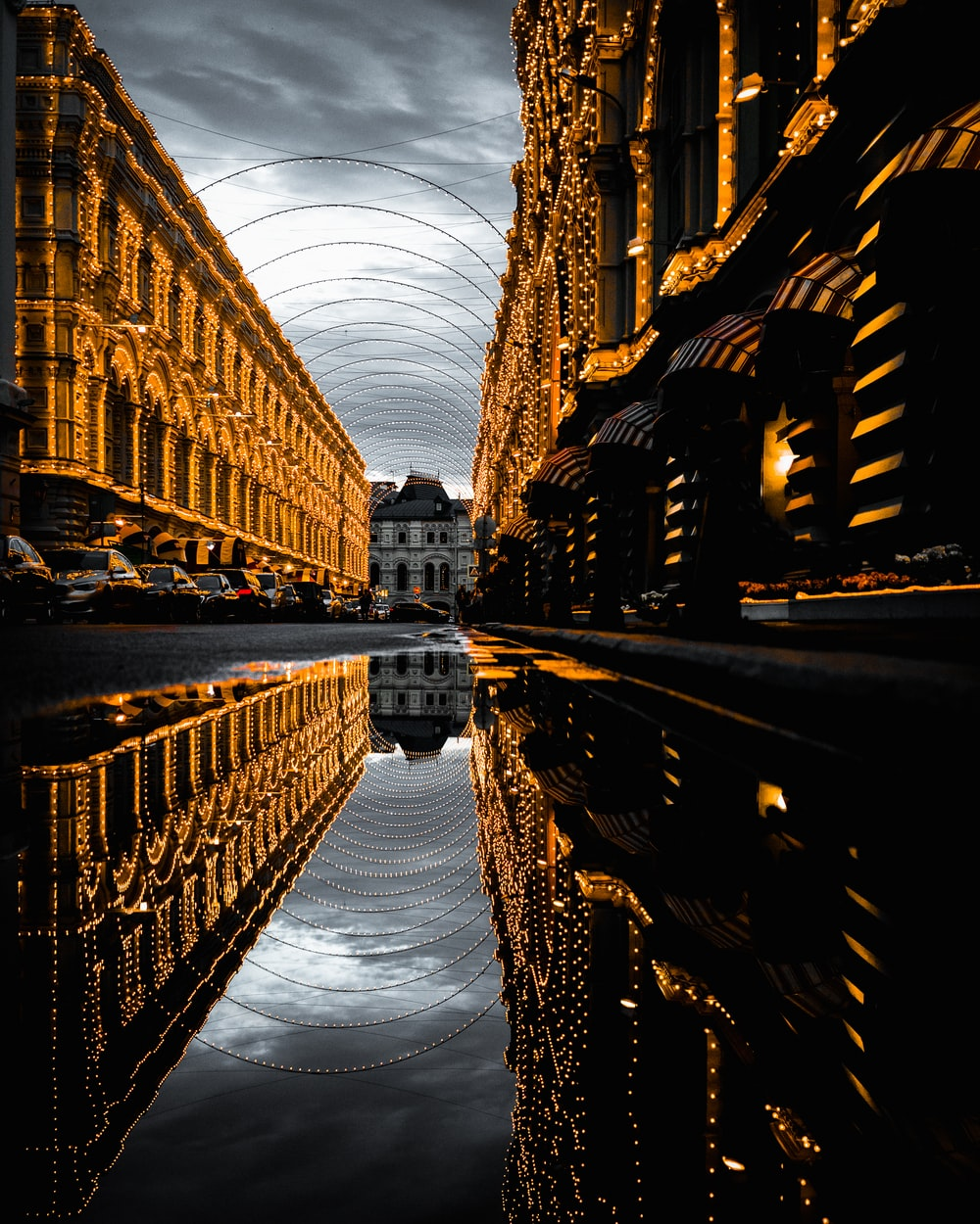 water on asphalt road with reflection of fully-decorated buildings under cloudy sky