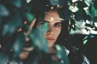 woman wearing blue denim top hiding beside grasses