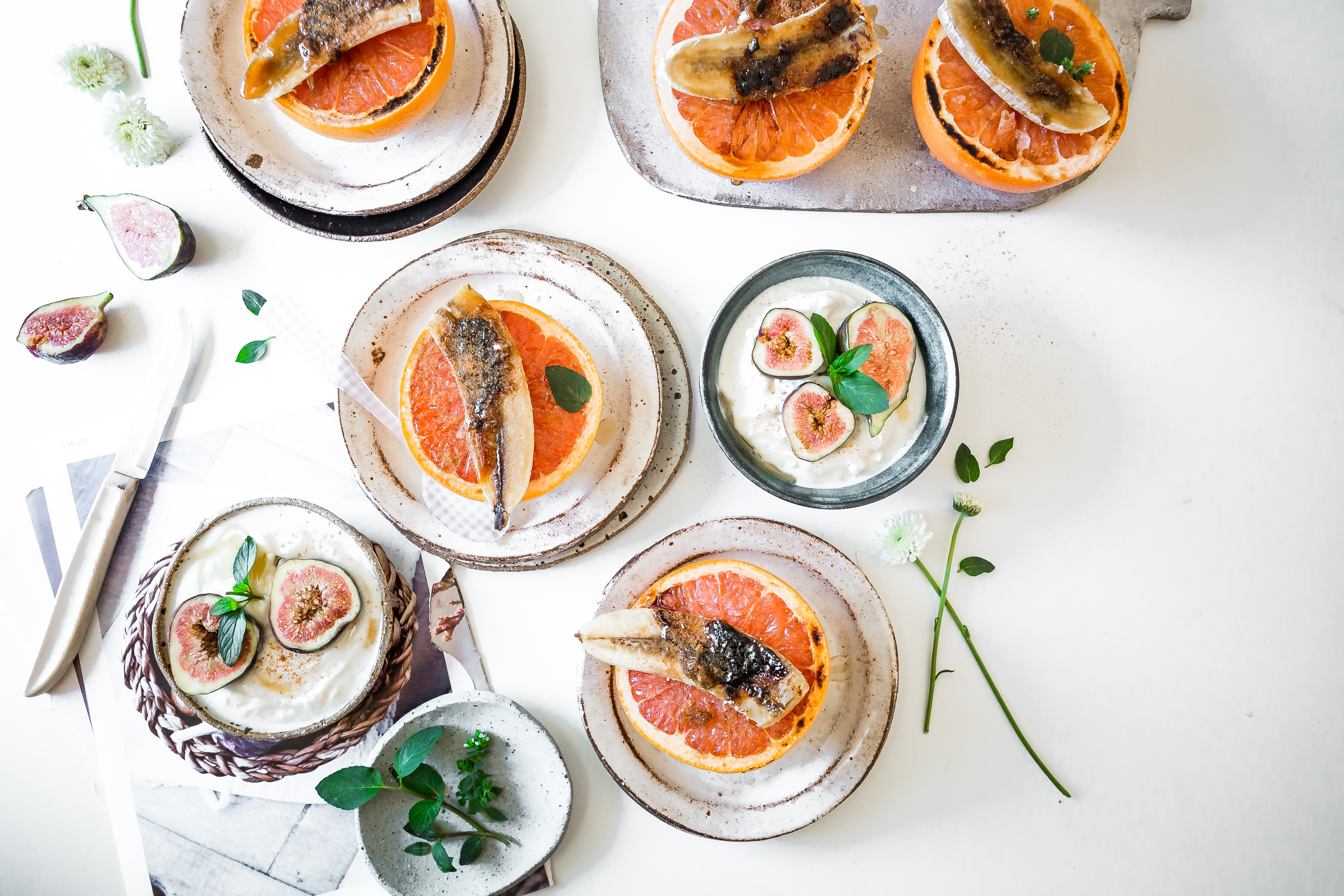 Overhead view of fresh grapefruit topped with nuts and figs over yogurt