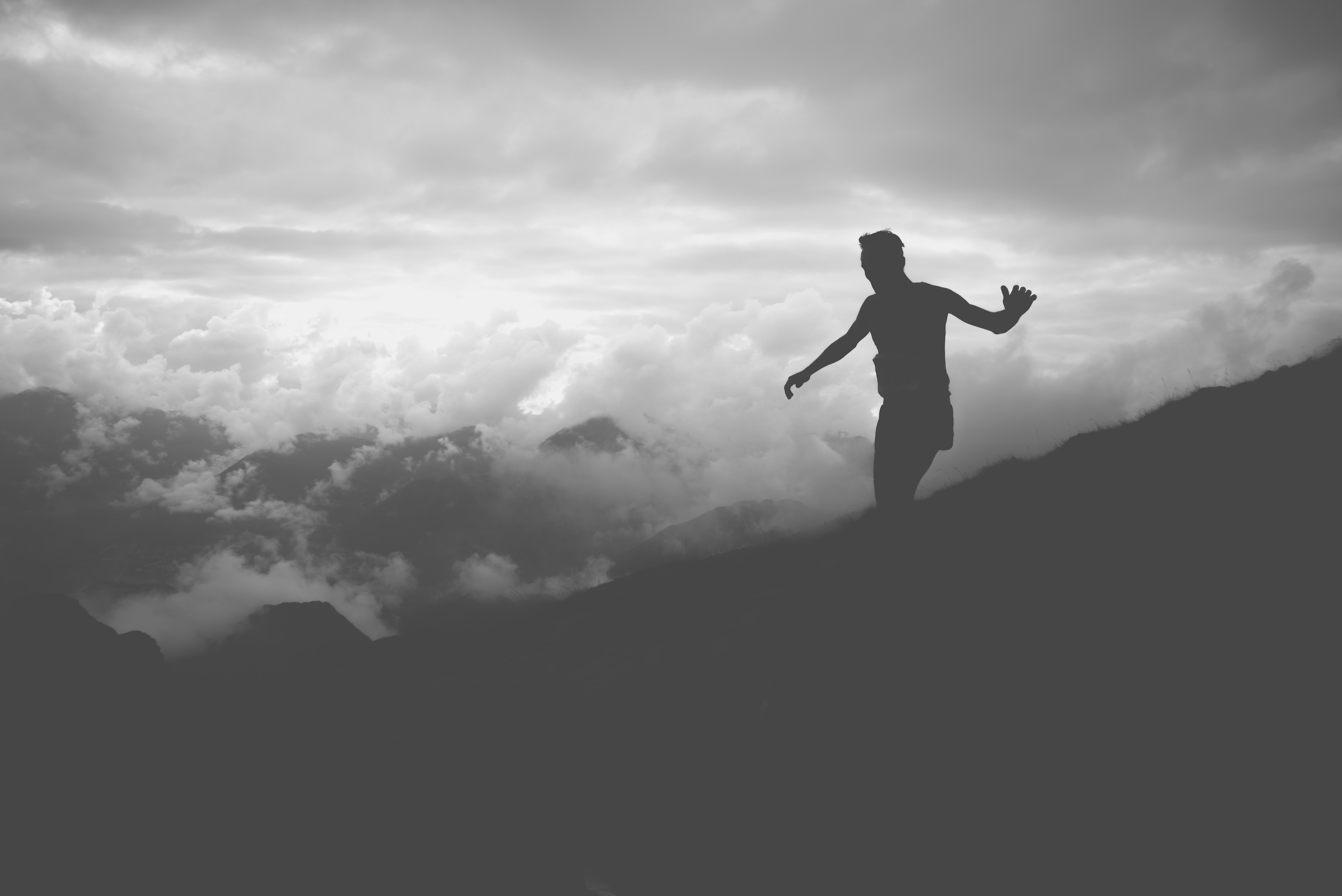 Black and white photo of a silhouette man walking on a hill with a clouded sky in the background