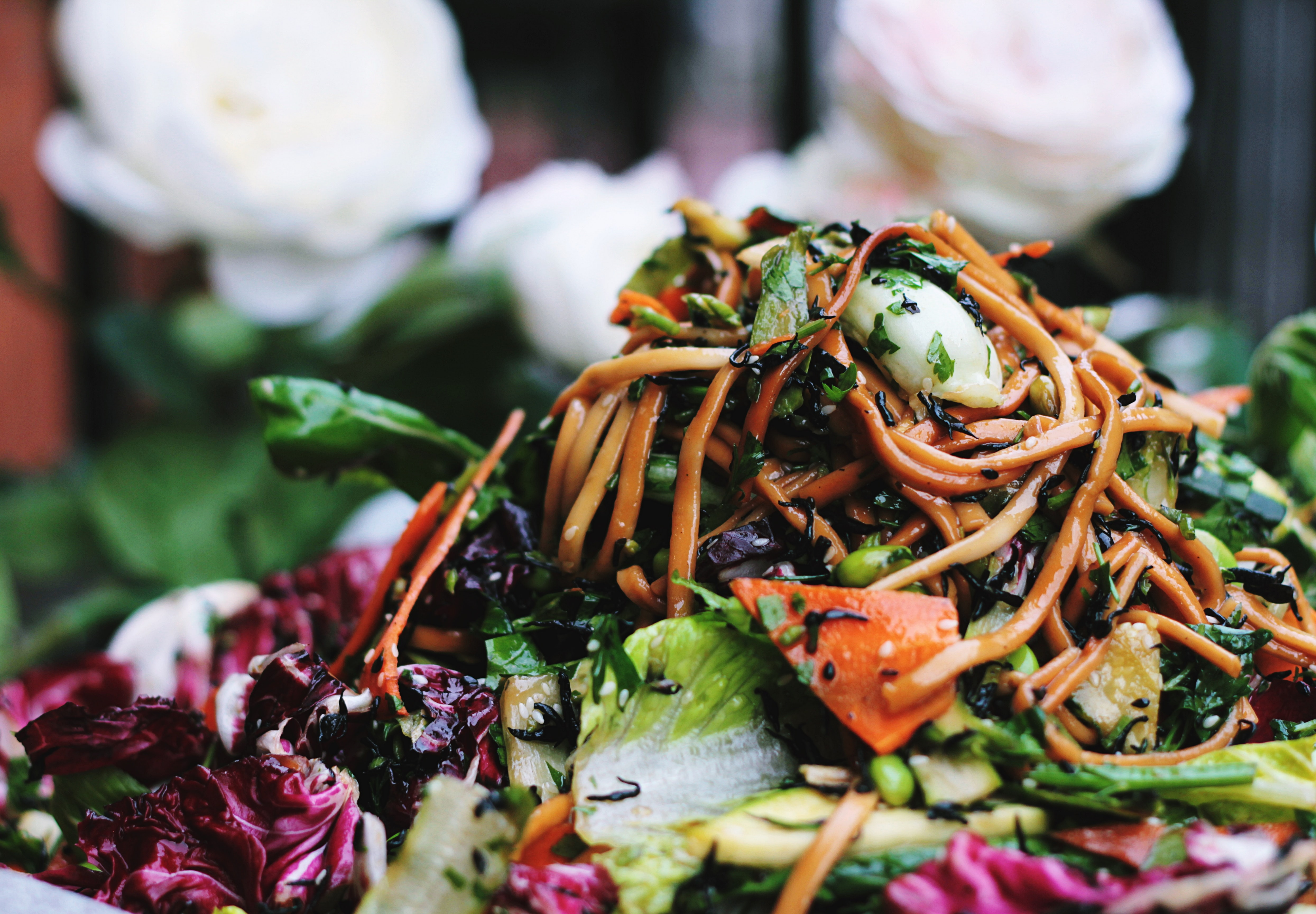 A macro of stir fry noodles with mixed vegetables and leaves