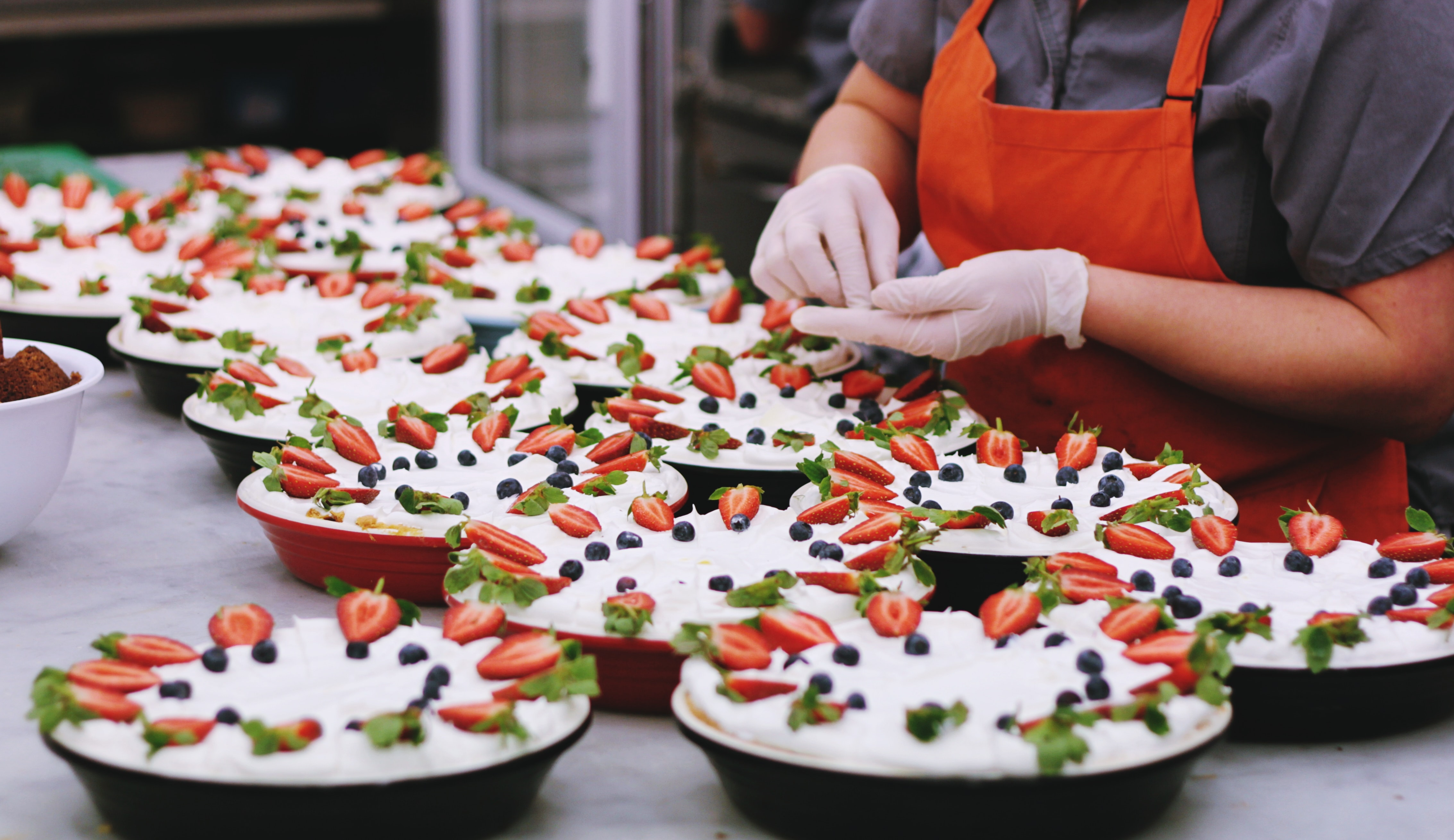 Baker prepares fresh cheesecakes topped with fruits