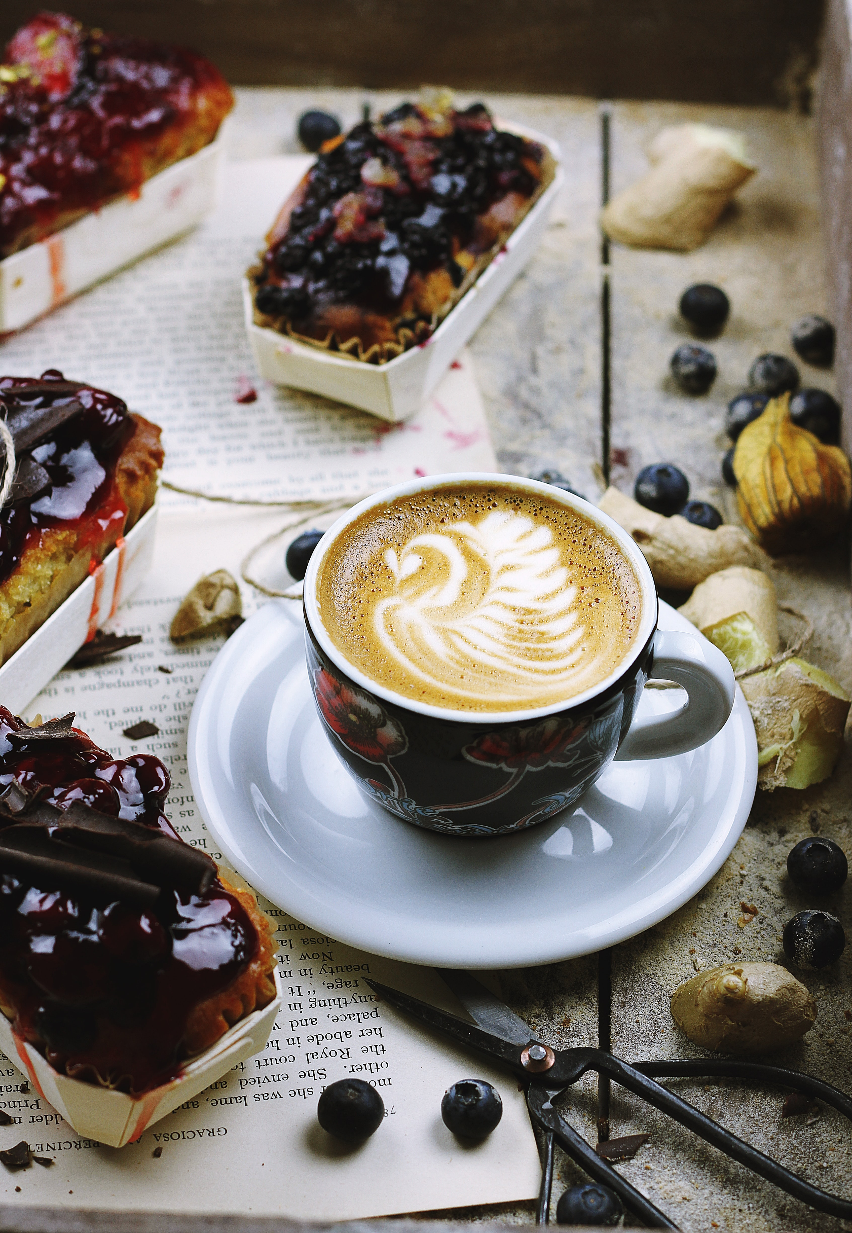 Latte artwork on white marble table with baked cake bar, fruit, scissors and grinder