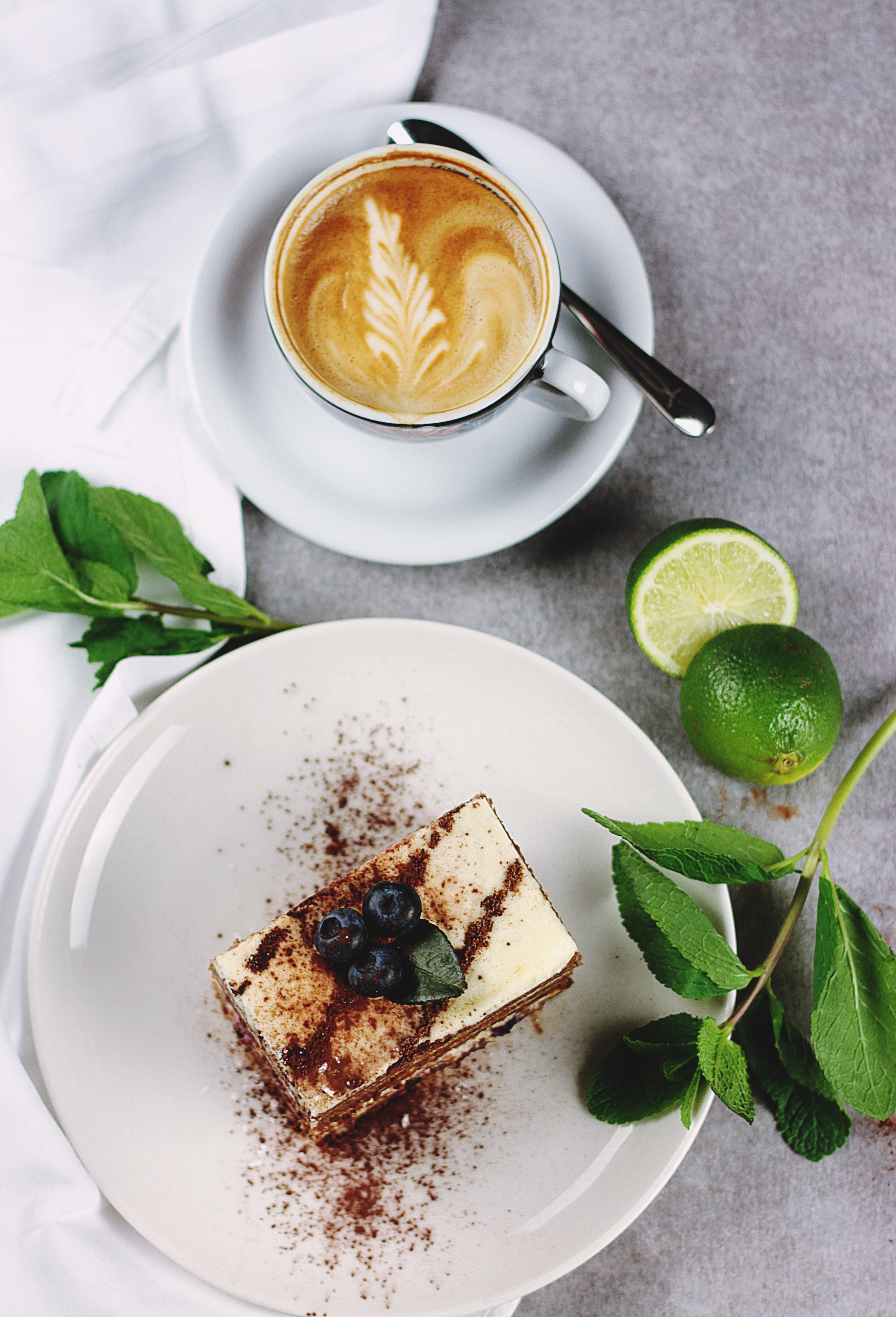 Coffee in white cup with foam artwork near plate with cake with dusting, mint and lime