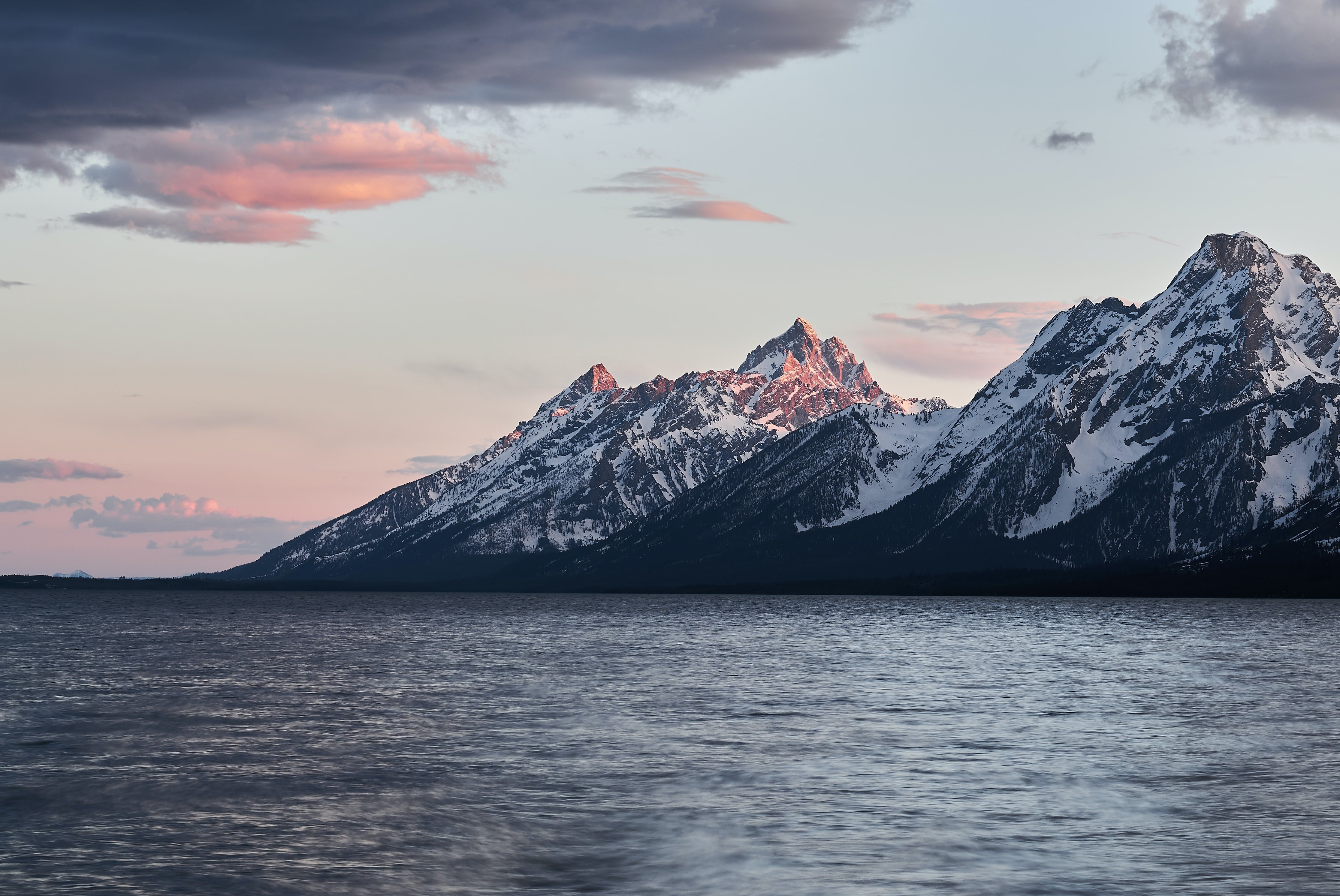 View from a lake on the snow-capped mountain peaks on the shore