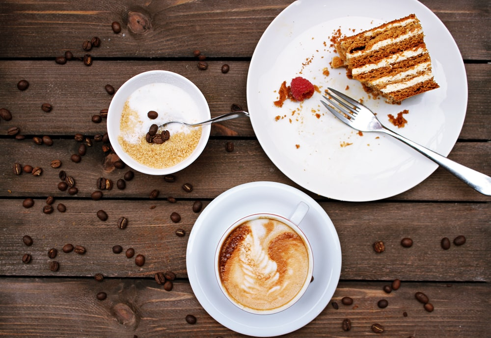 slice of cake on plate beside cappuccino