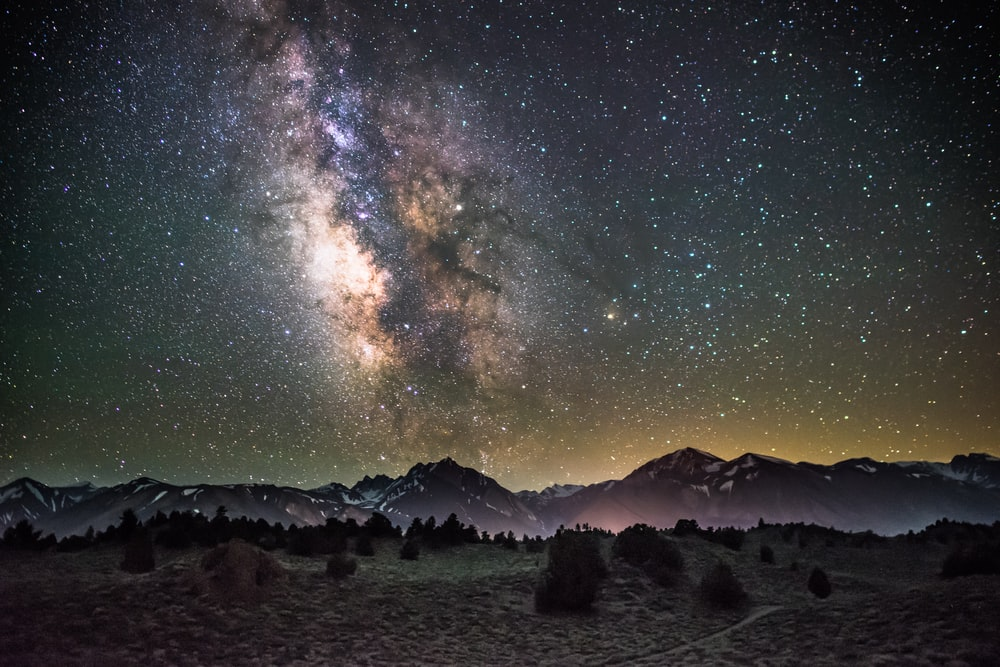 silhouette of mountains under milky way galaxy