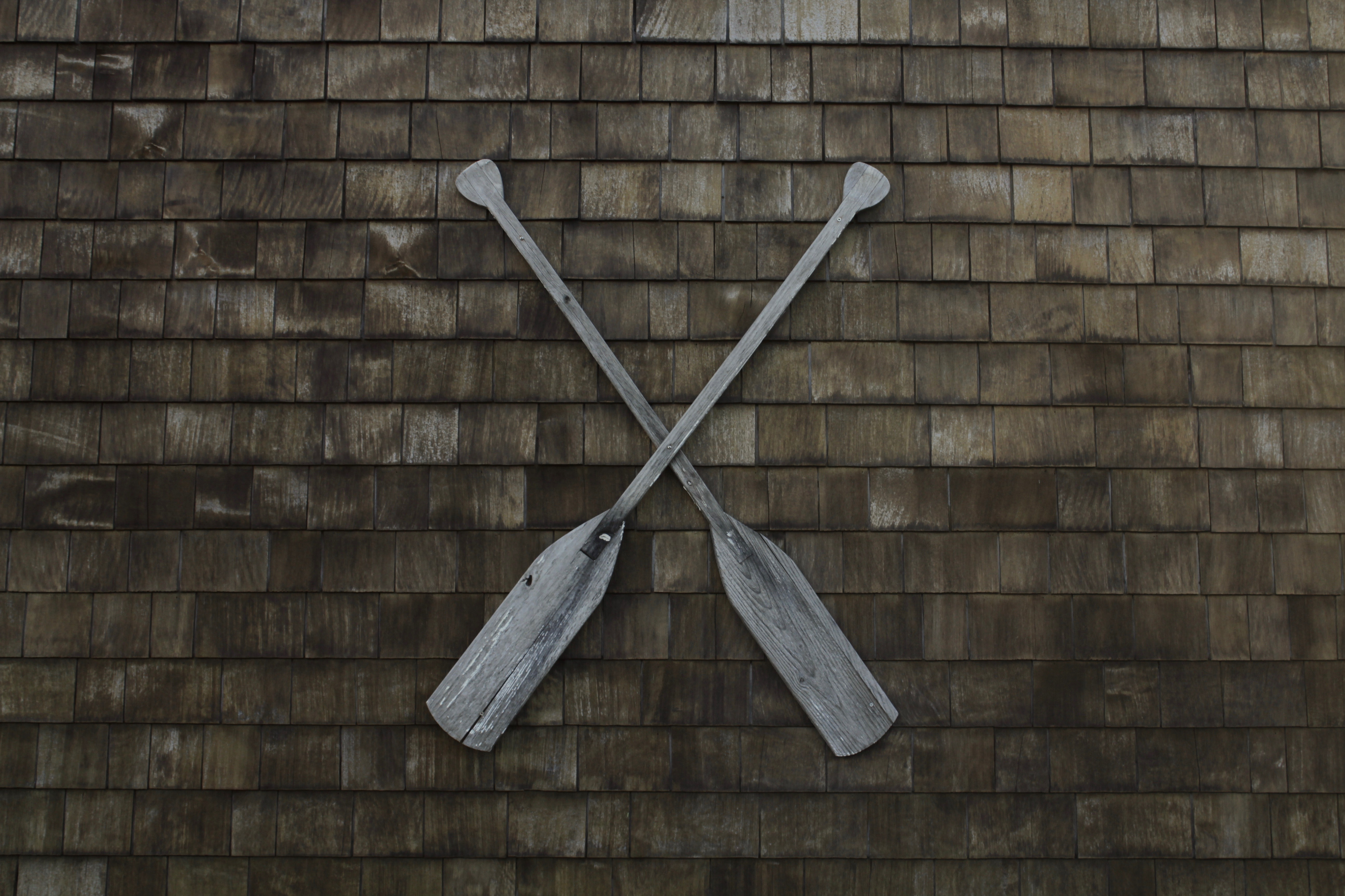 Two wooden oars crossed together on a wall
