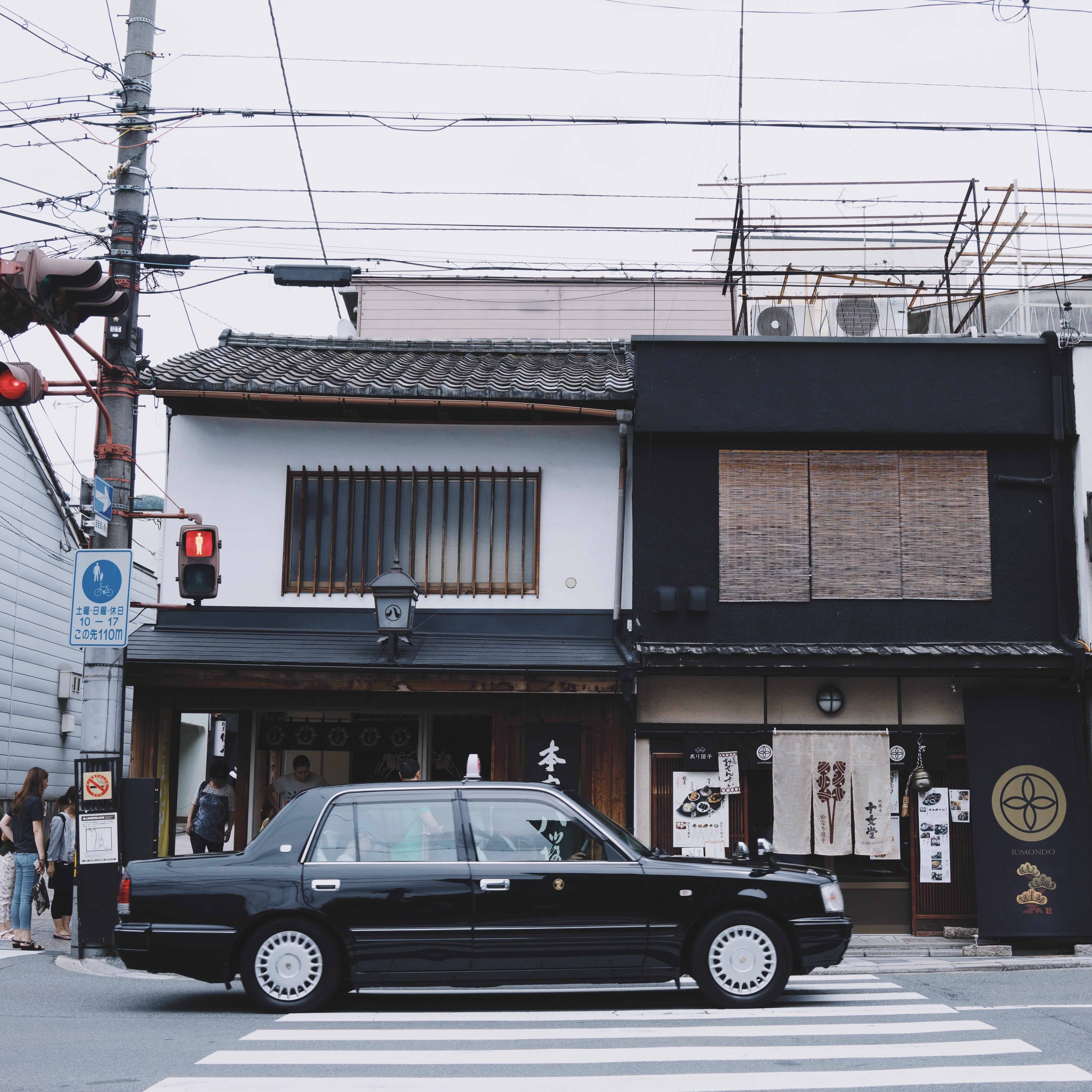 Old black car drives down an urban street by houses