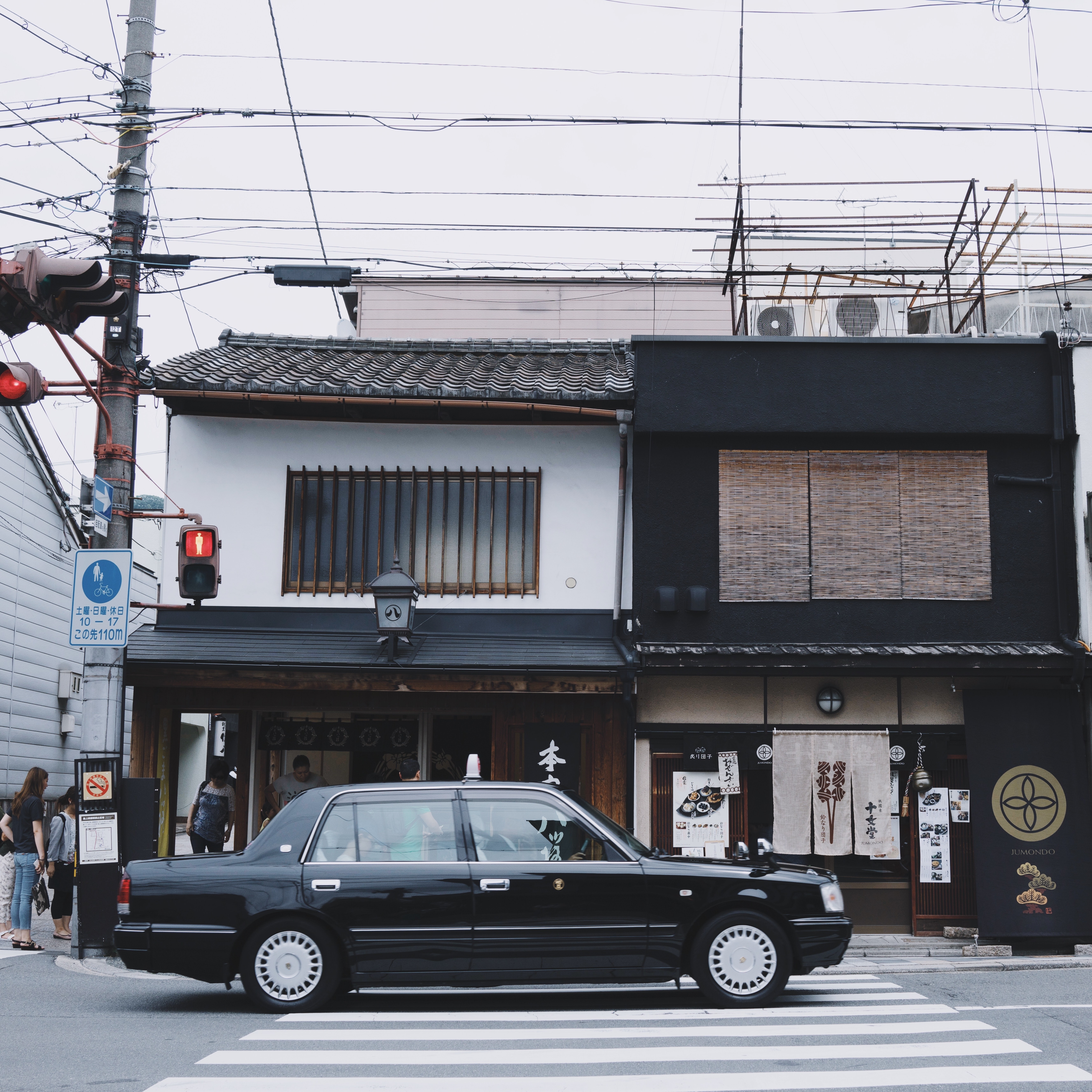 black sedan in front of black and white 2-storey house