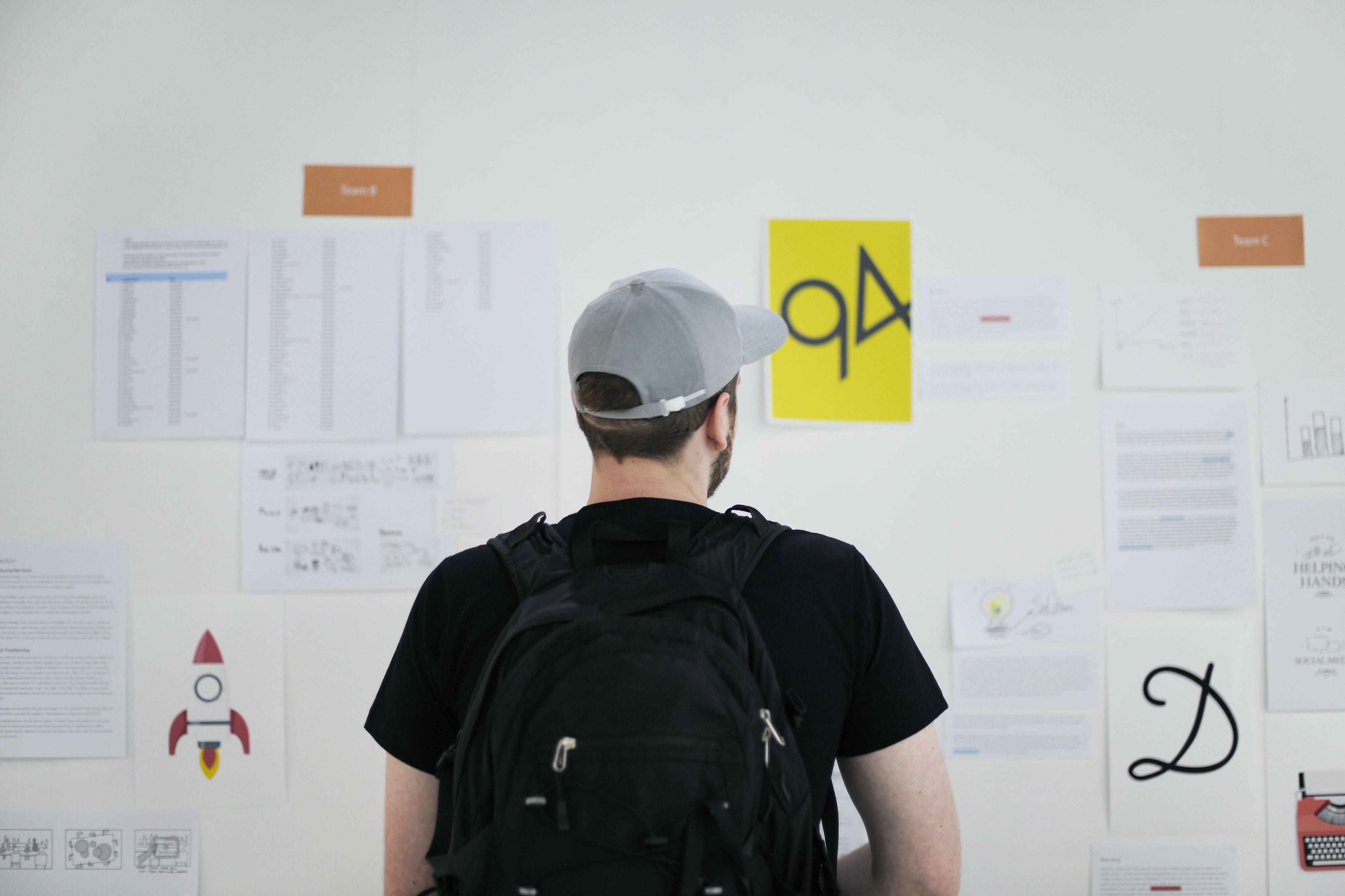 A man wearing a black backpack and baseball cap, staring at work related documents on the office wall