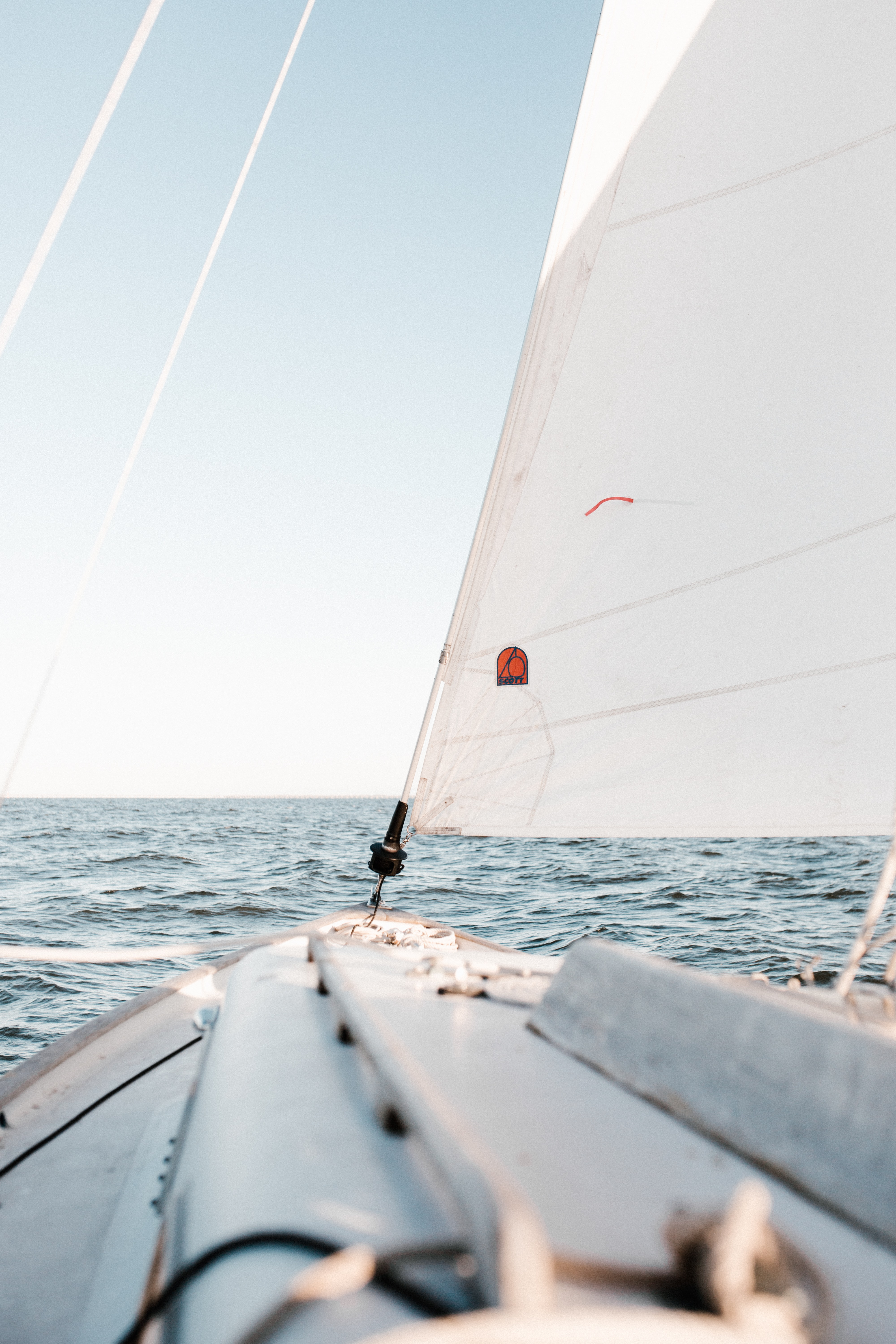 A view from a sailboat on a choppy sea and the clear sky above