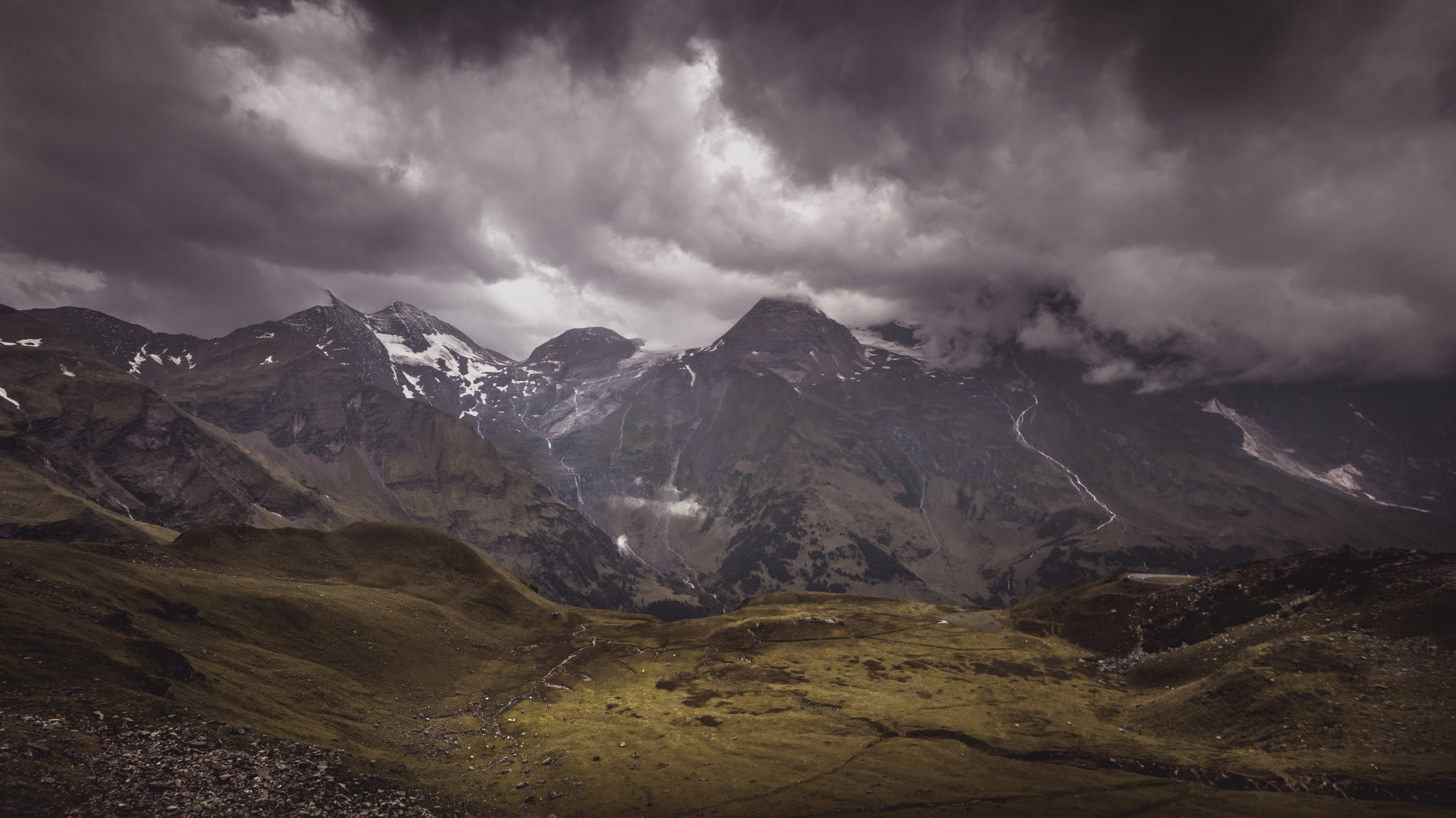 A snow-topped mountain massif under dense clouds
