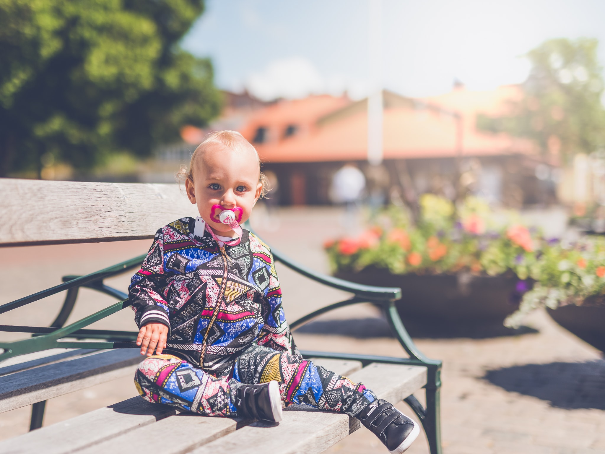 Baby with a pacifer in a geometric trendy onesie on a park bench