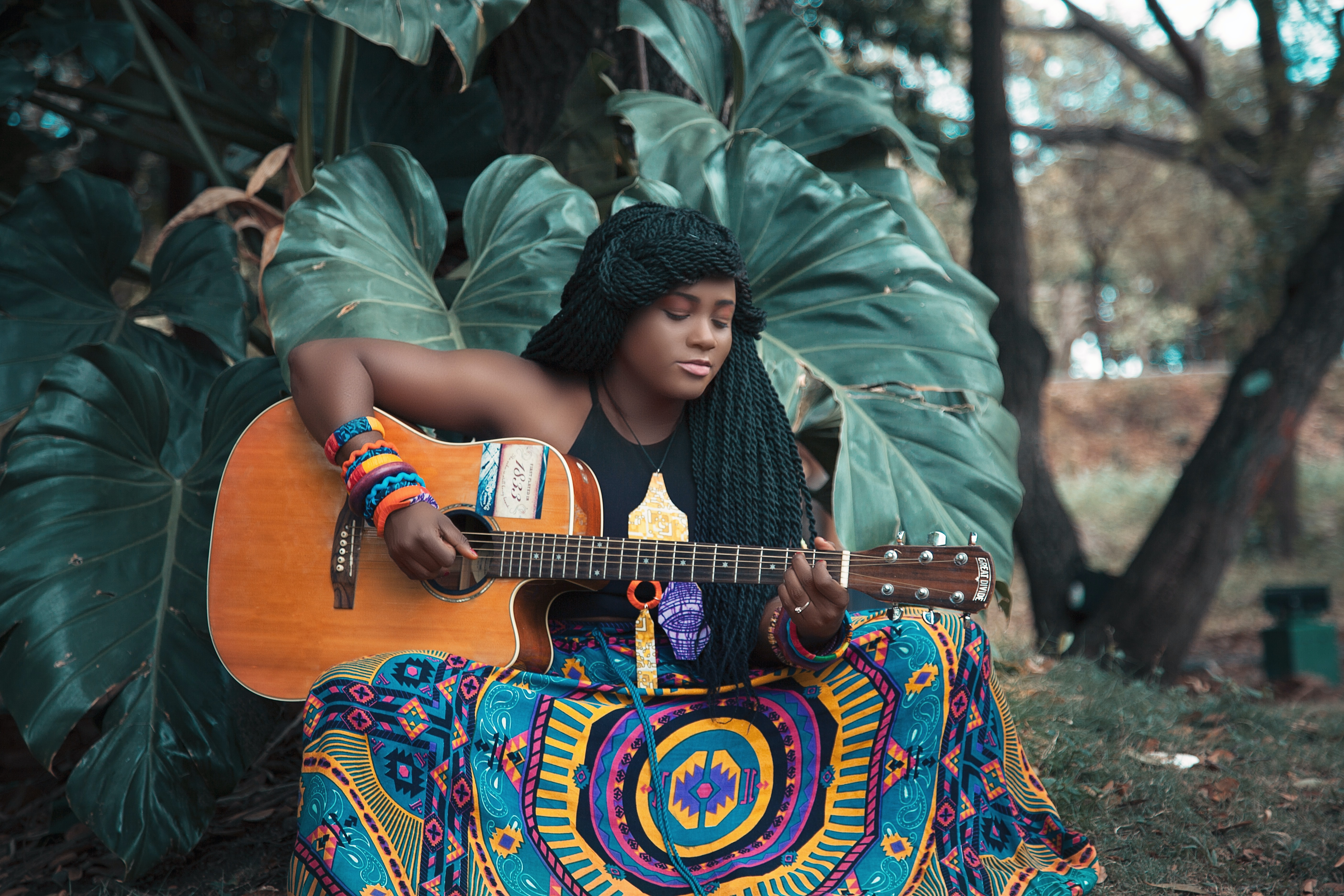 A woman with long twists in her hair and an ornate skirt plays a guitar outdoors