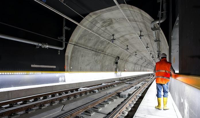 man standing beside train rail