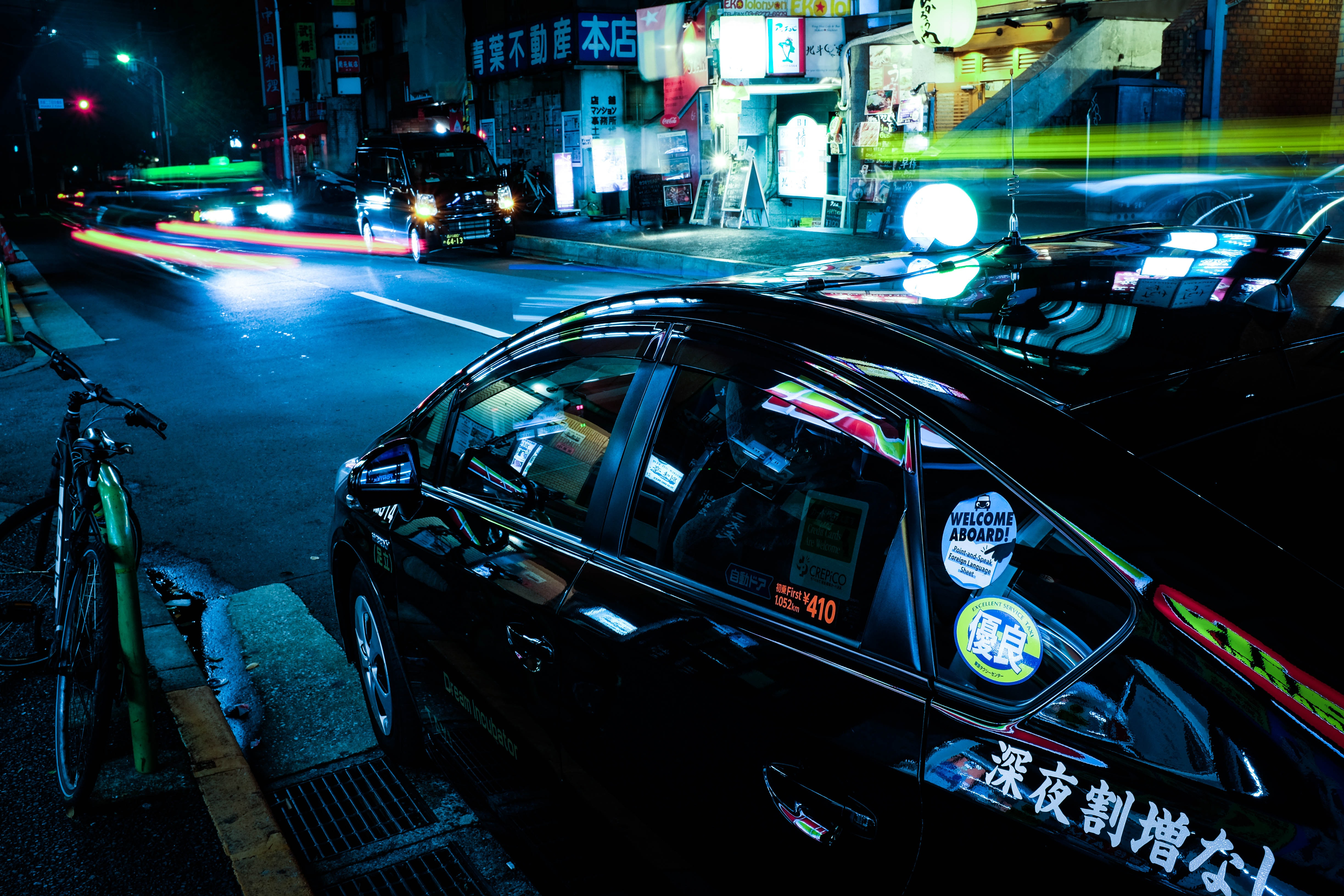 A taxi parked near city nightlife.