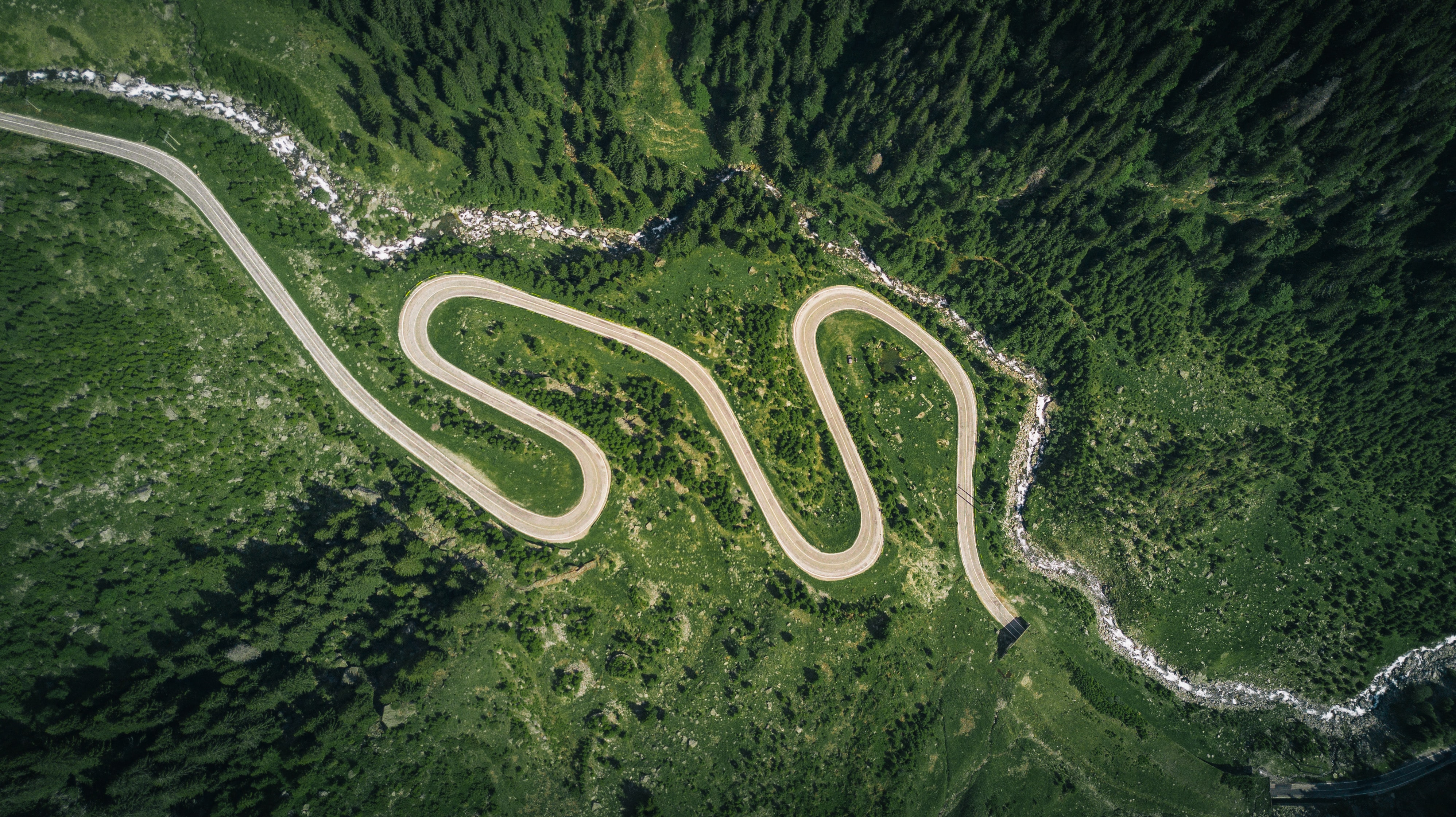 A drone shot of a zigzagging road leading into a tunnel