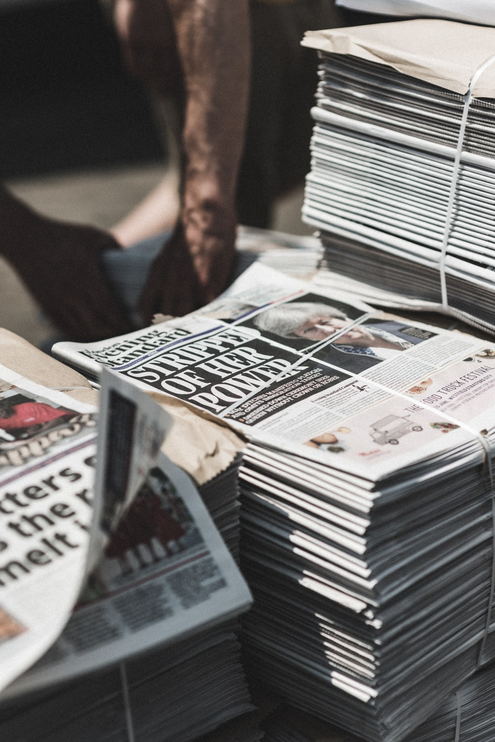 shallow focus photography of piles of newspapers