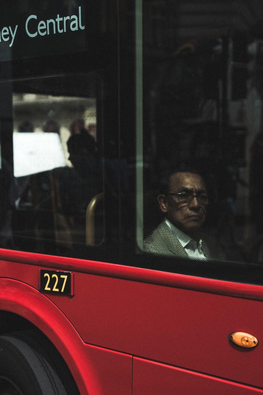 man sitting near vehicle window at daytime