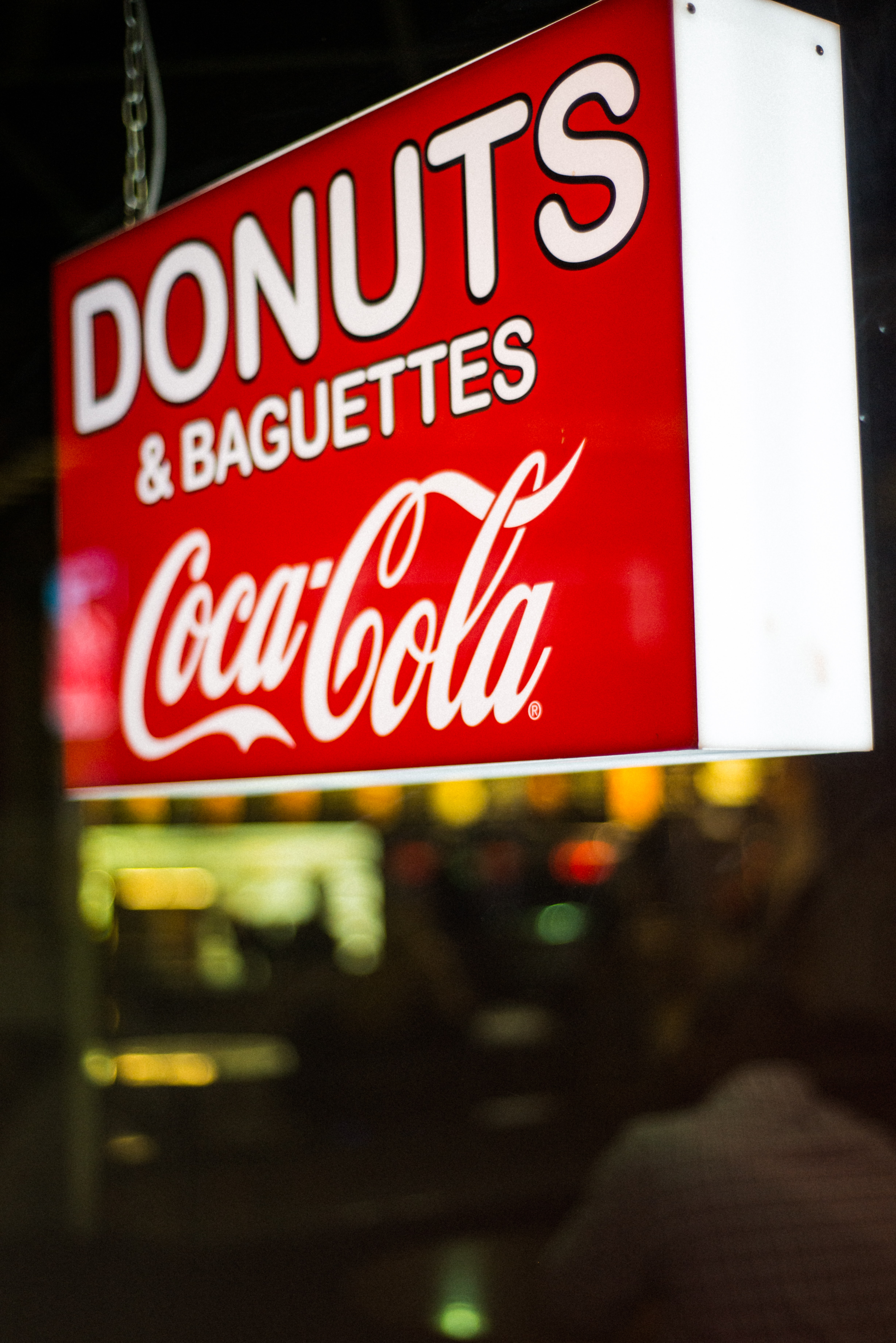 close photography of Donuts & Baguettes Coca-Cola signage