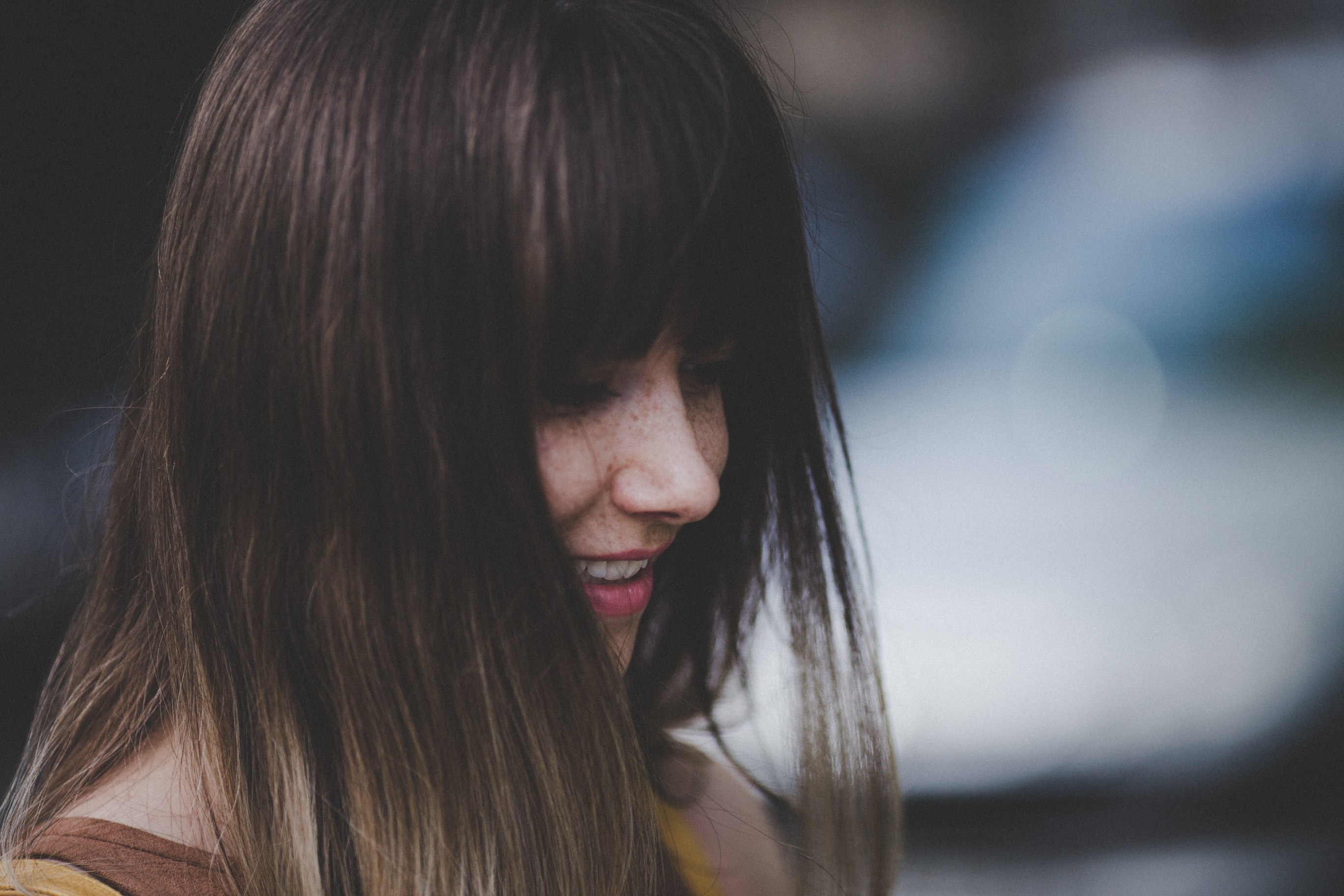 A woman with long brown hair and bangs smiles while looking downward against a blurry background