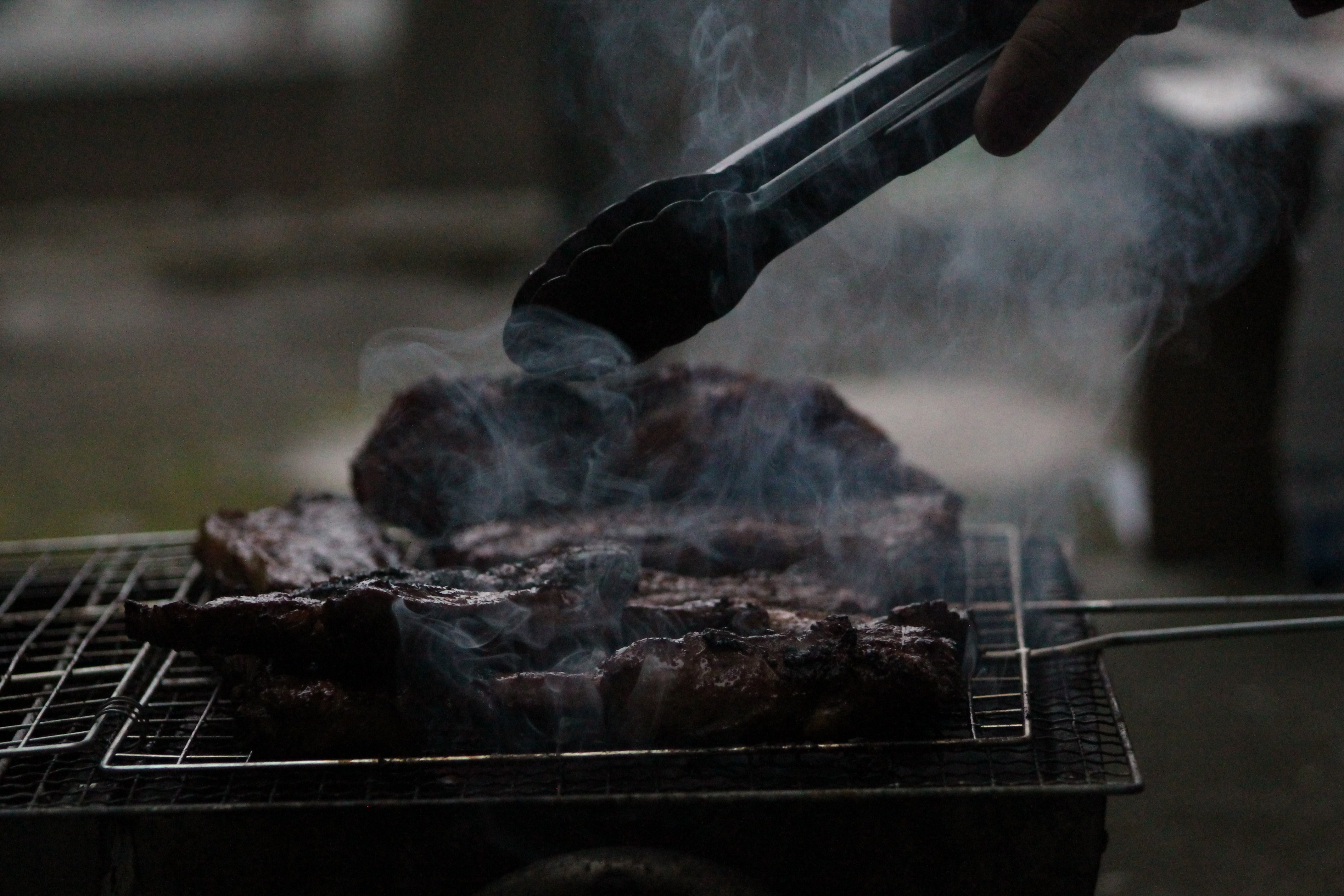 Grilling barbecued ribs on a smoky grill