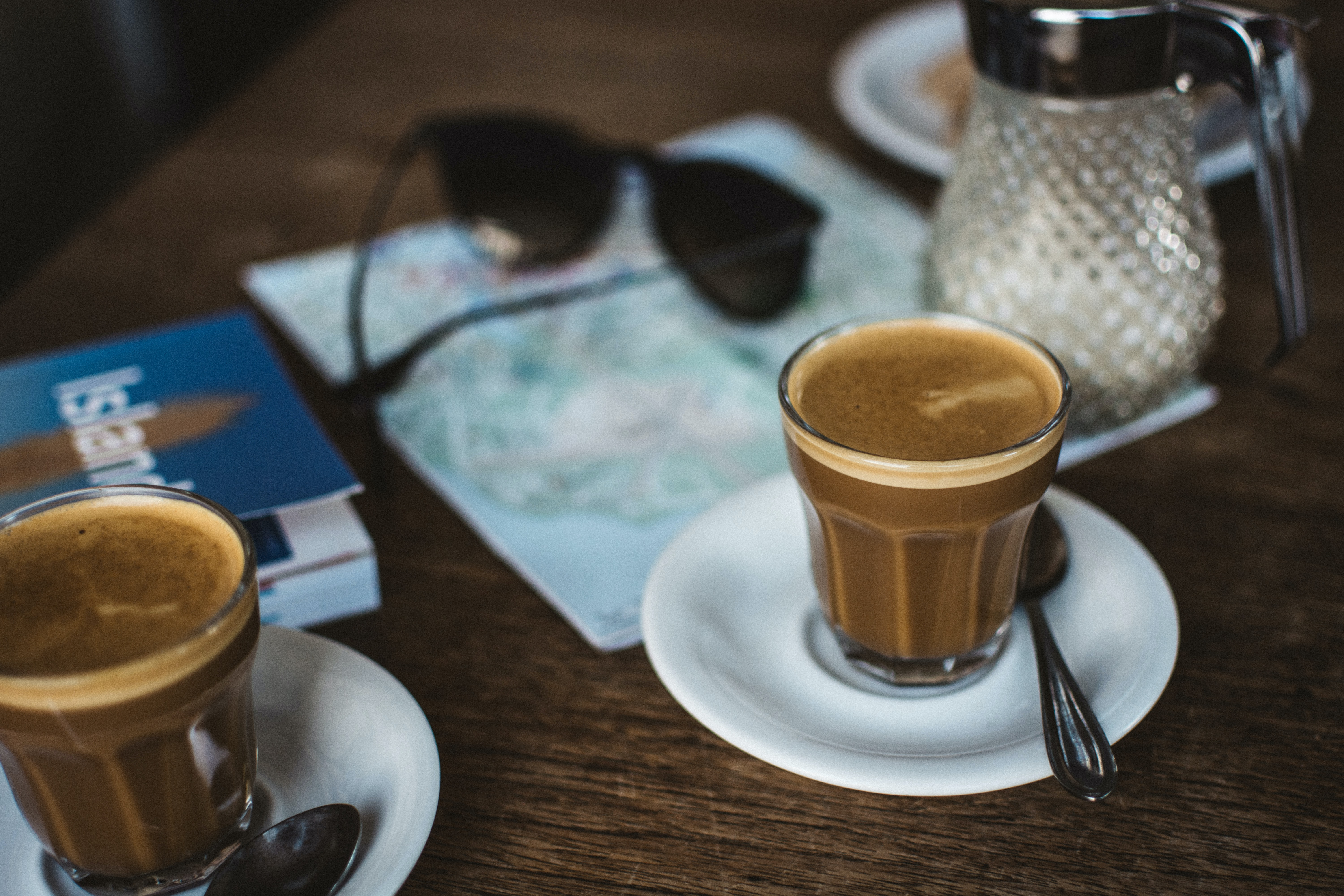 Latte in a clear glass on a white saucer with a spoon with sunglasses and a map on the table