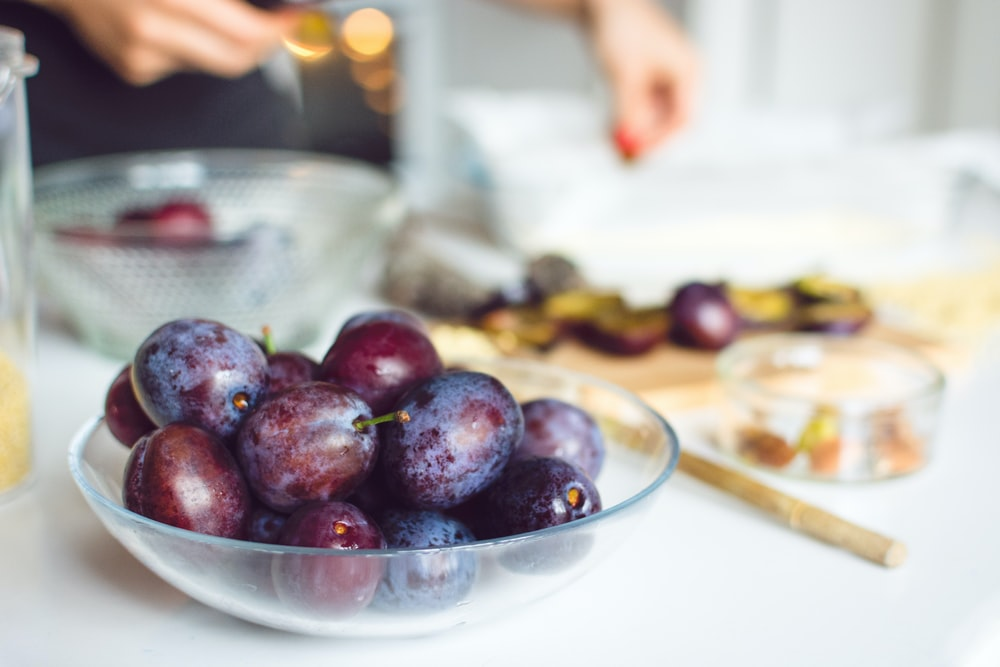 bowl of red grapes on white tabletop