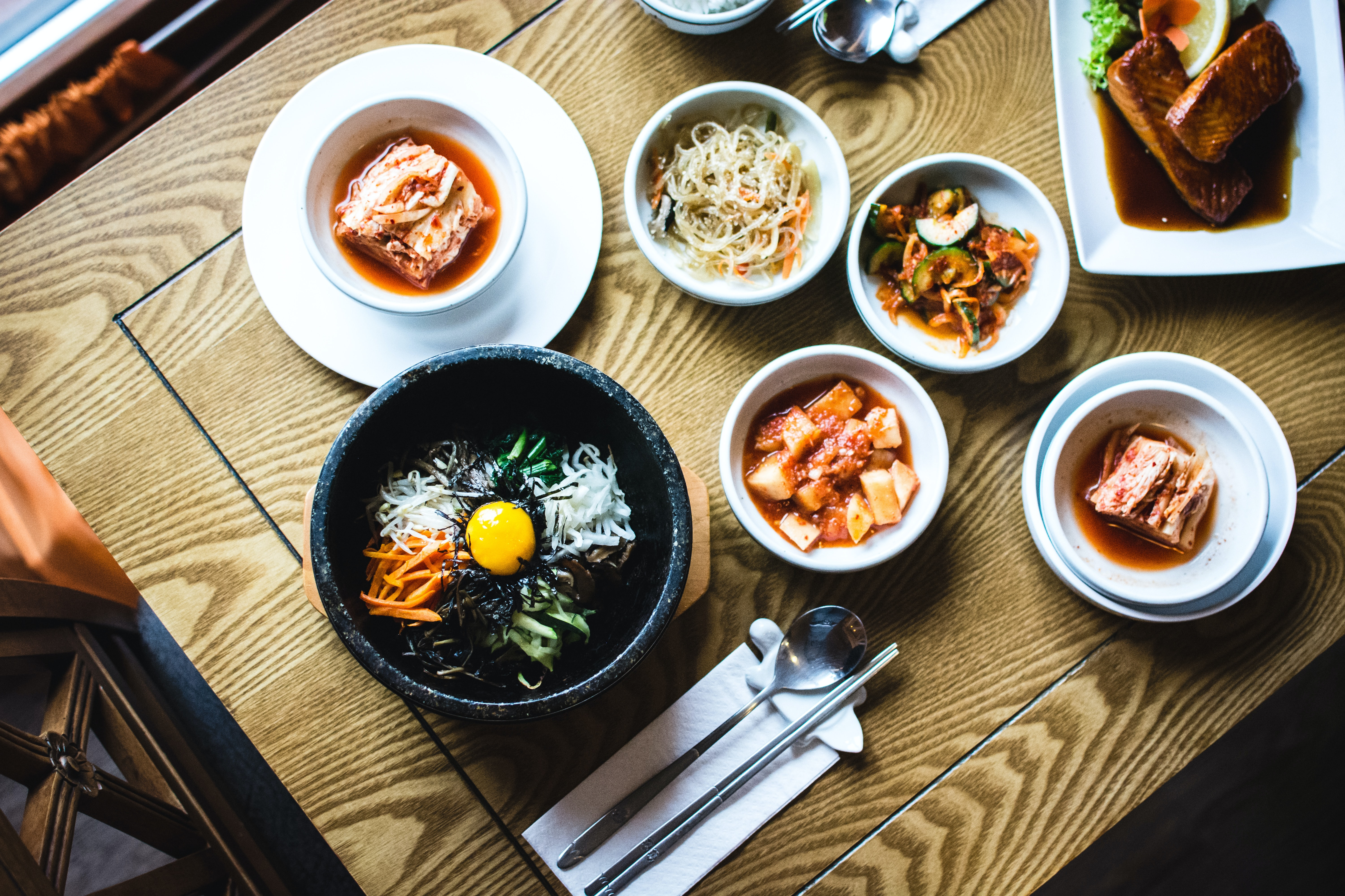 Overhead shot of table with bowls of pho, kimchi, and Korean food