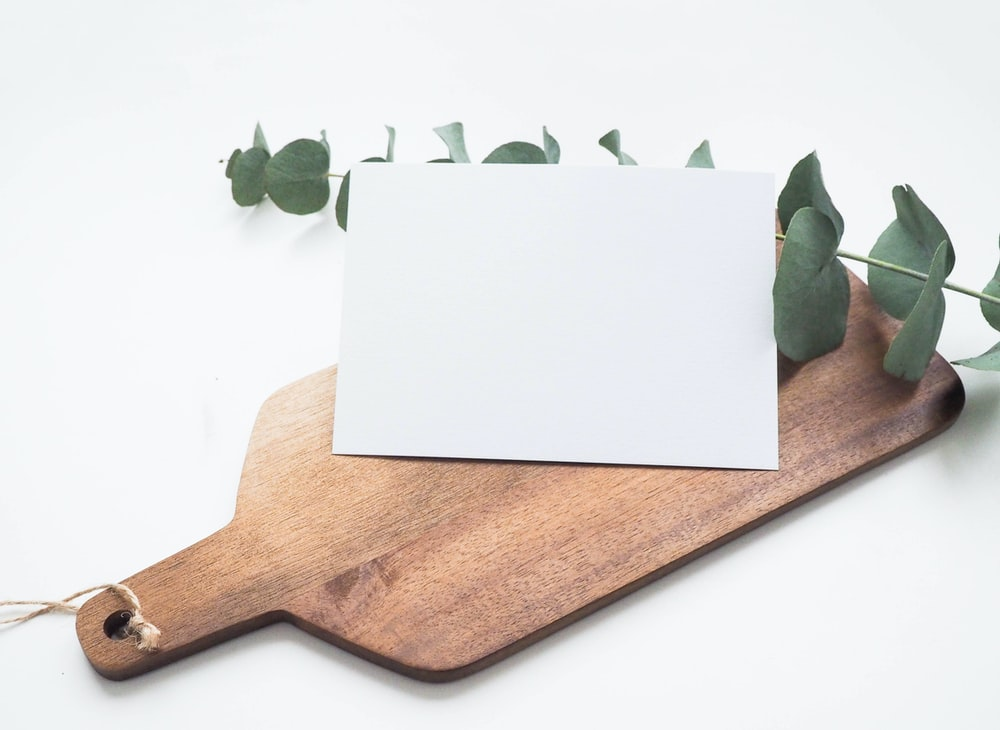 A wooden cutting board with a branch and piece of paper on top.