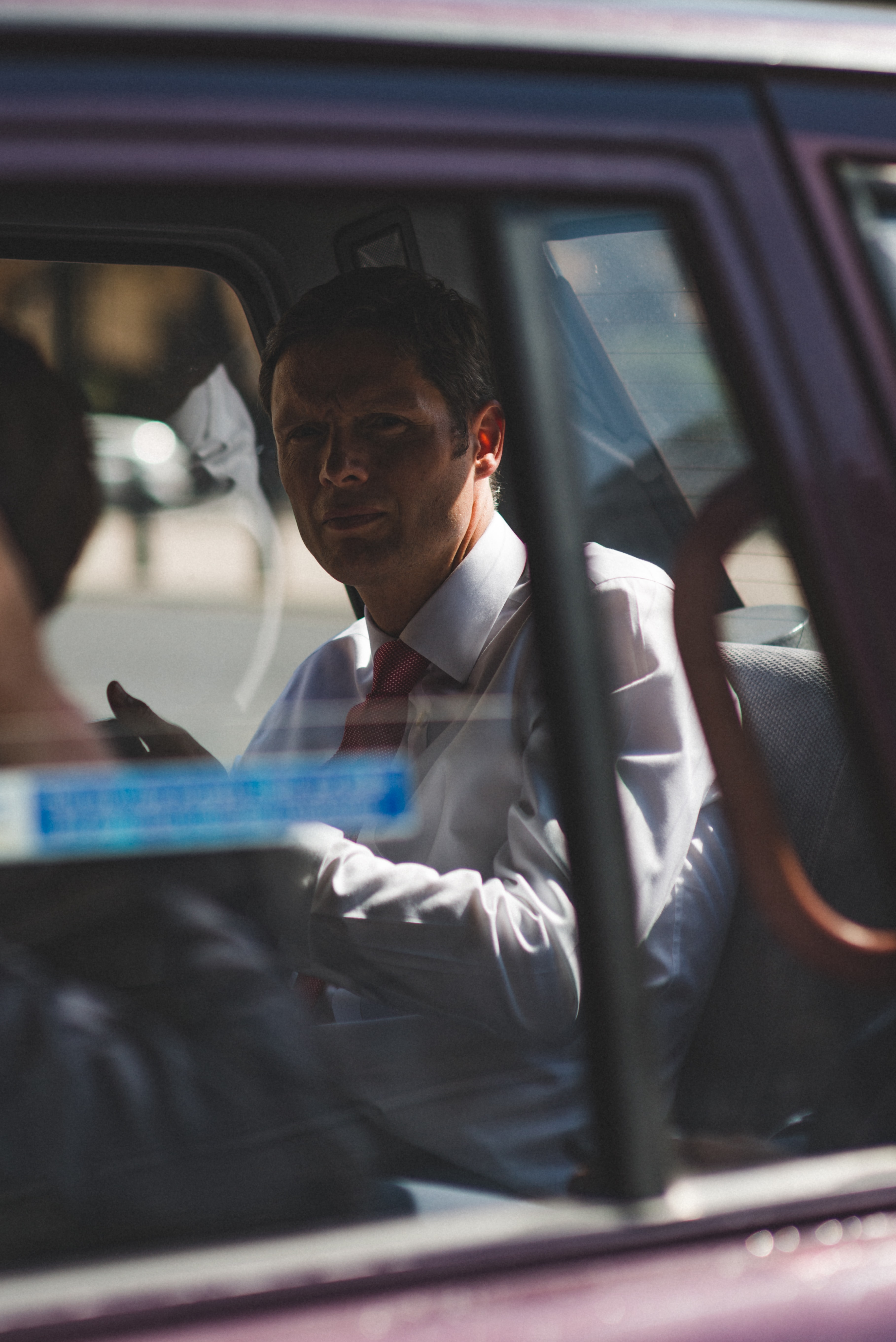 A man in a white shirt and a red tie in the back seat of a car