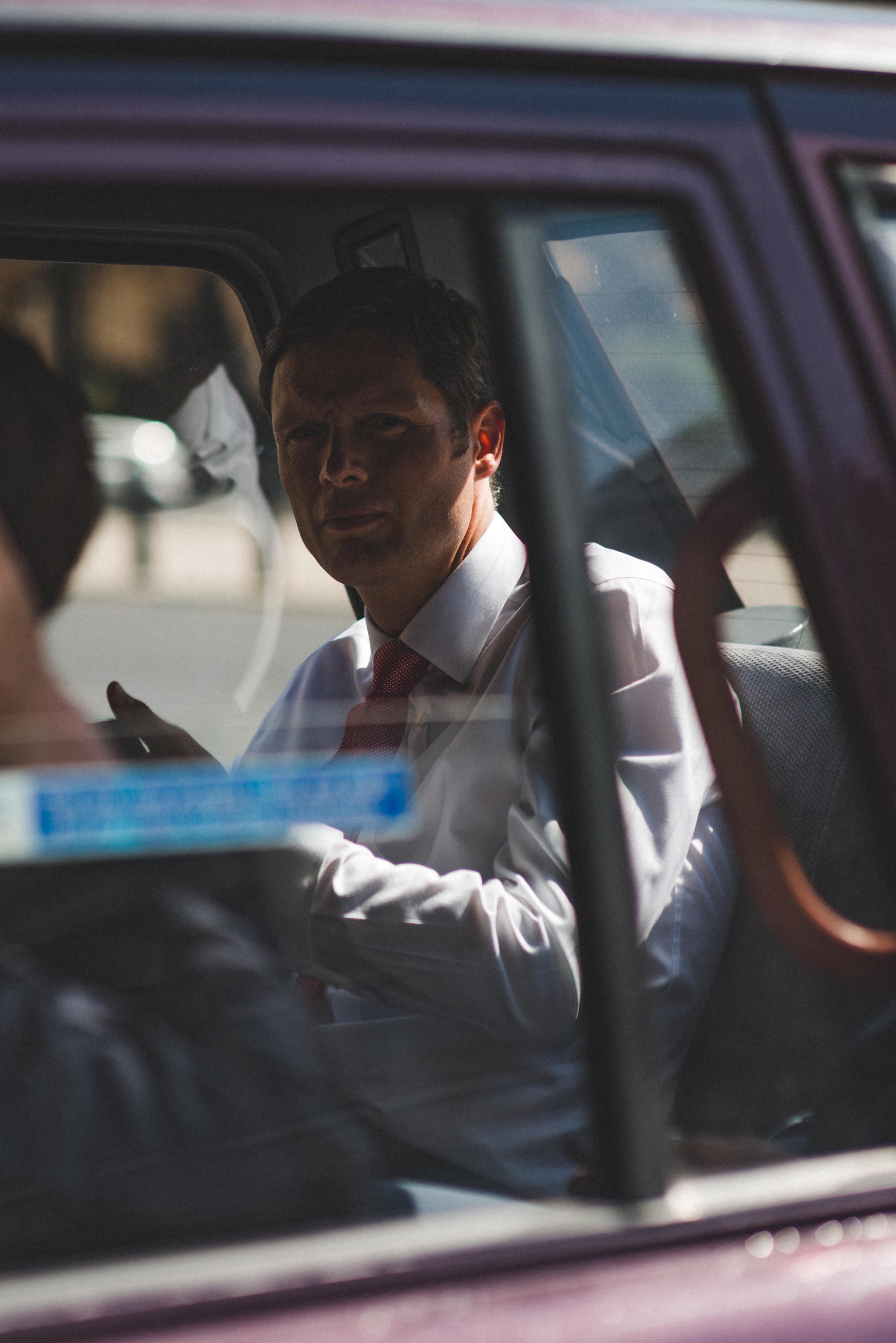 man in white dress shirt sitting inside vehicle