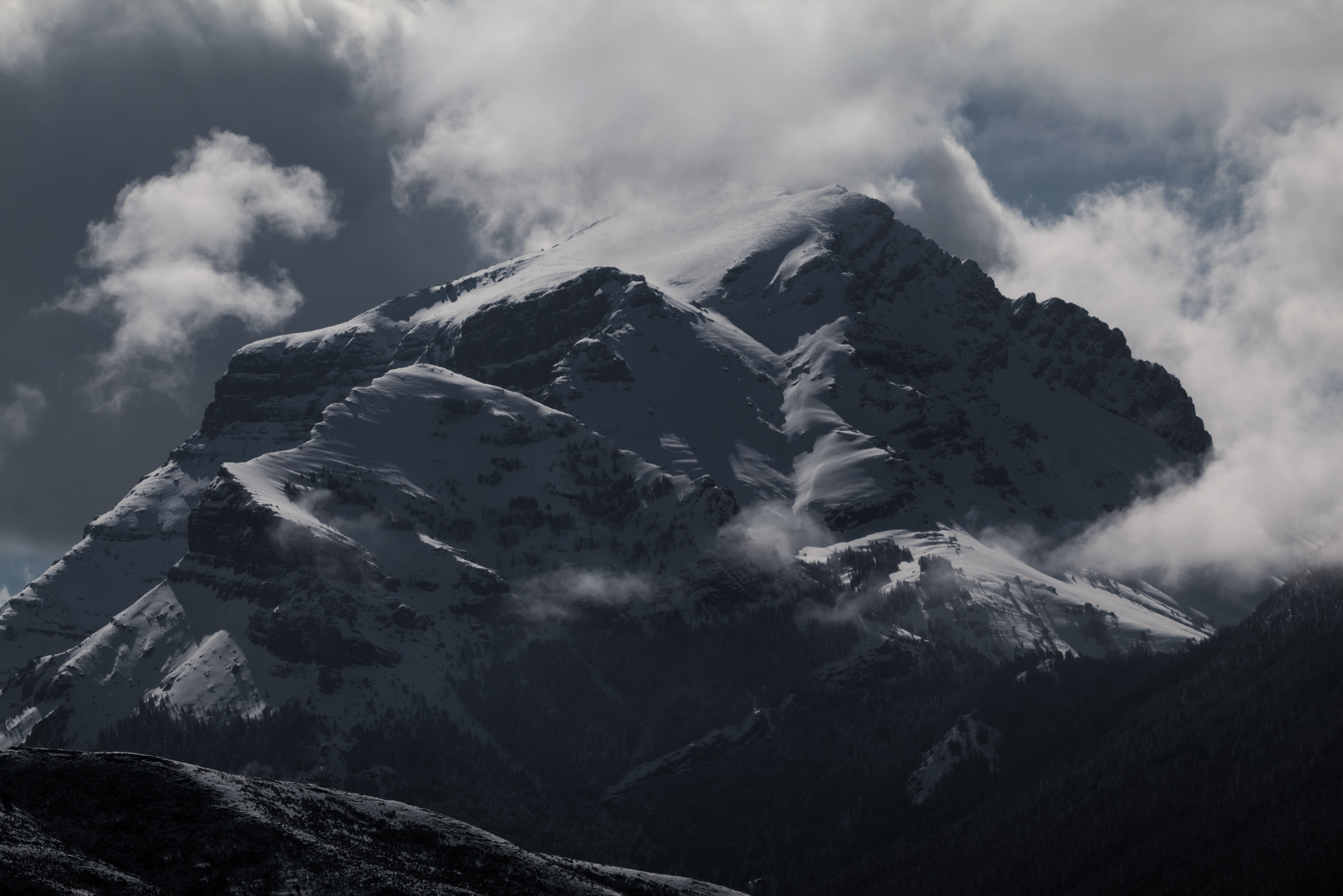 A dim shot of an imposing mountain peak shrouded by clouds