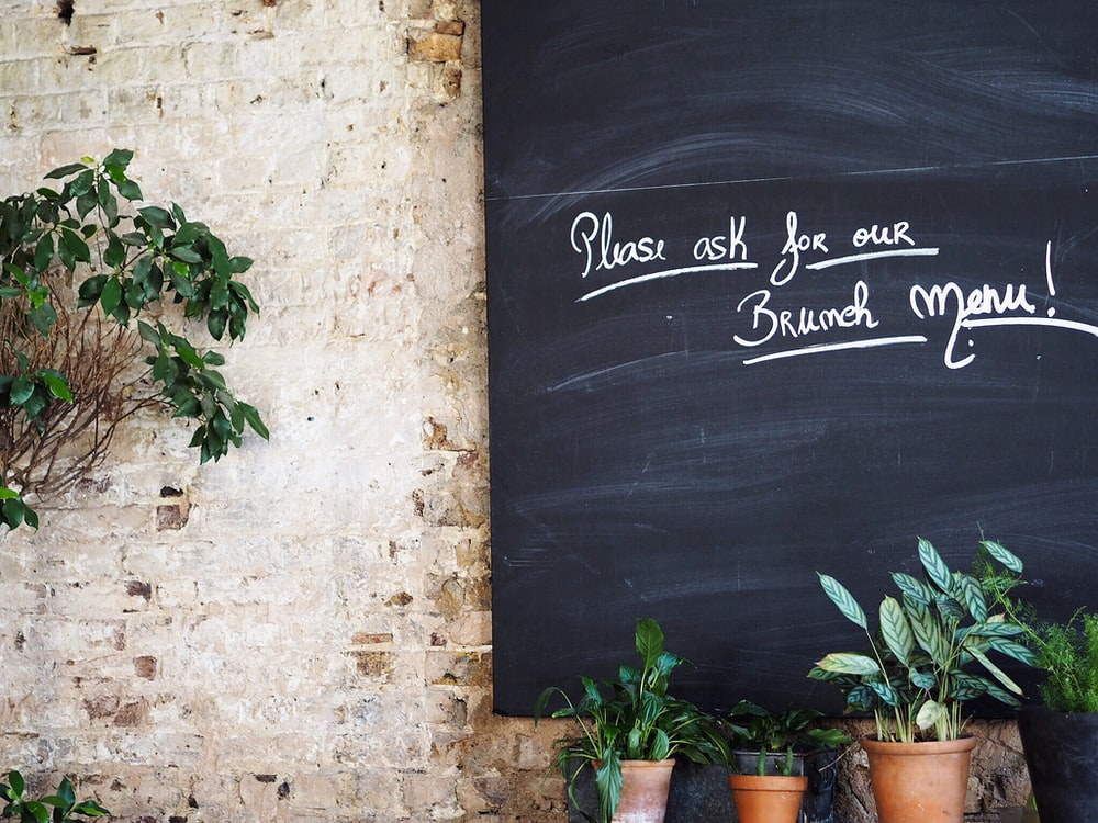 black board with pleas ask for our brumeh meru! text beside green potted plants