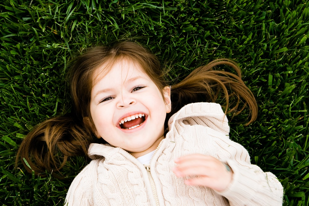 girl smiling while lying on grass field at daytime