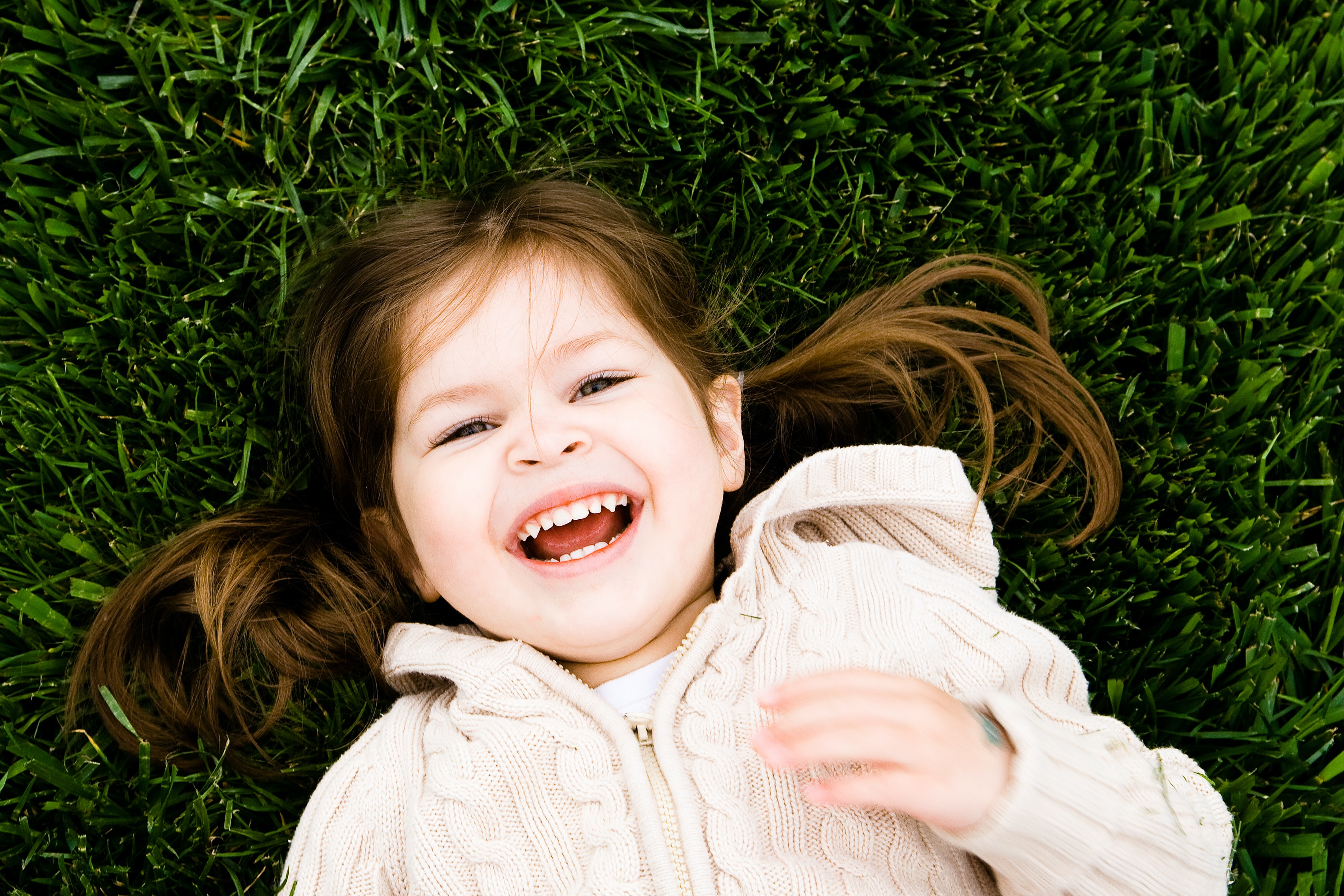 A toddler lays on green grass as she laughs happily