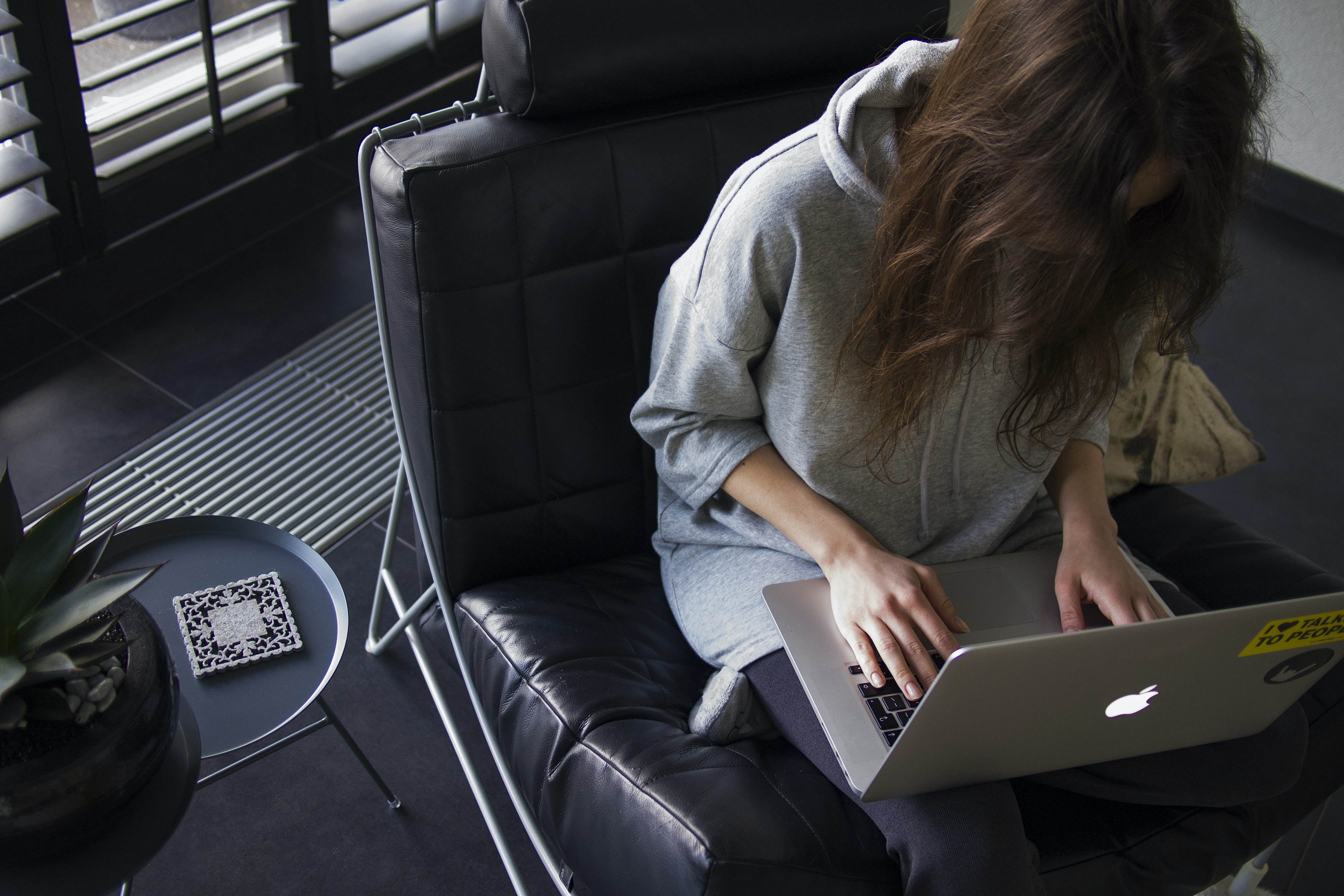woman in blue chambray long-sleeved top sitting on black leather chair with silver MacBook on lap