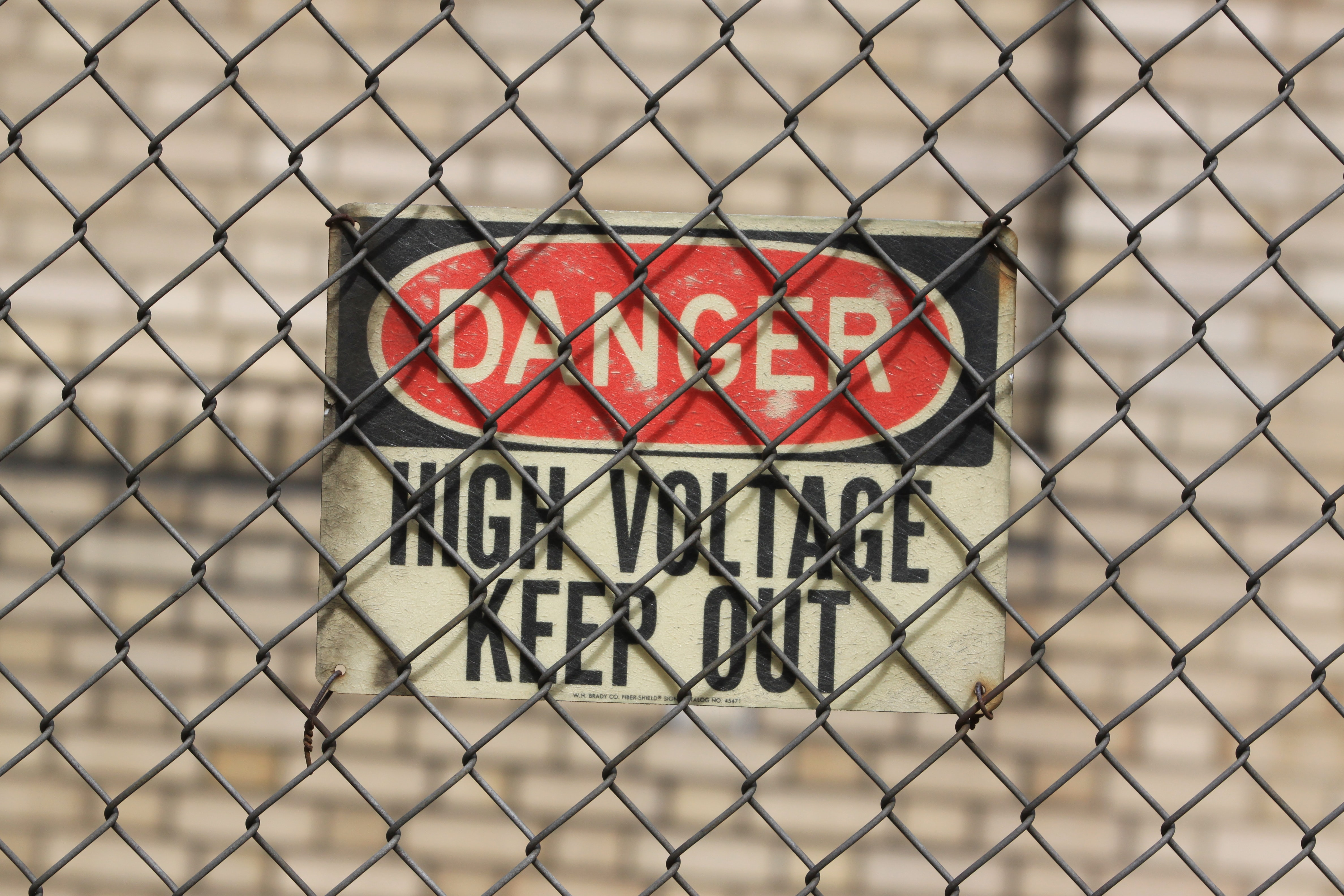 Danger sign behind a chainlink fence warns of high voltage
