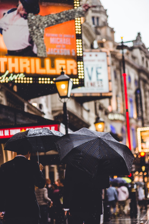 people walking while holding umbrella